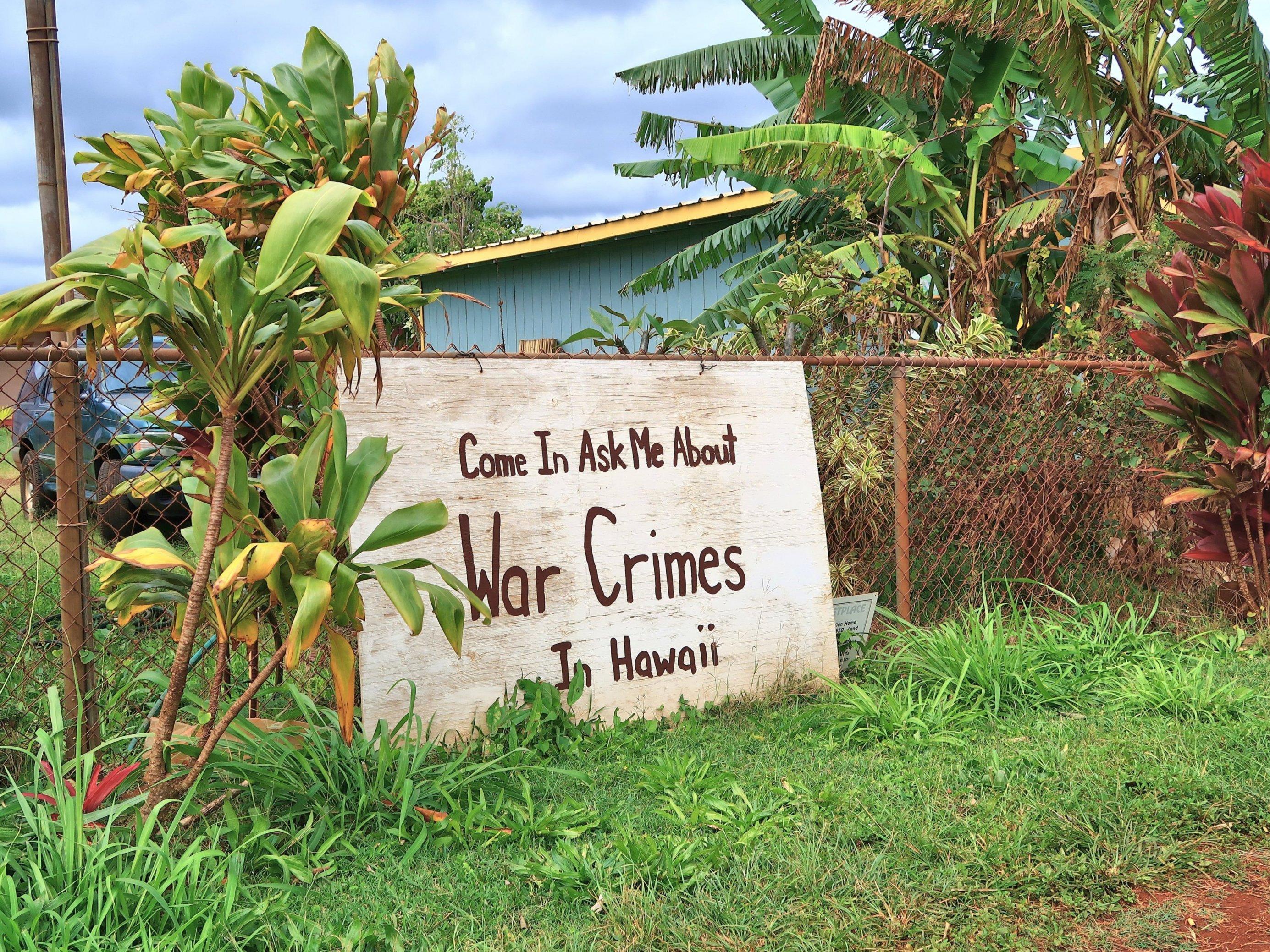 """Ein Schild lehnt an einem Zaun, Aufschrift: """"Come in and ask me about war crimes in Hawaii"""""""