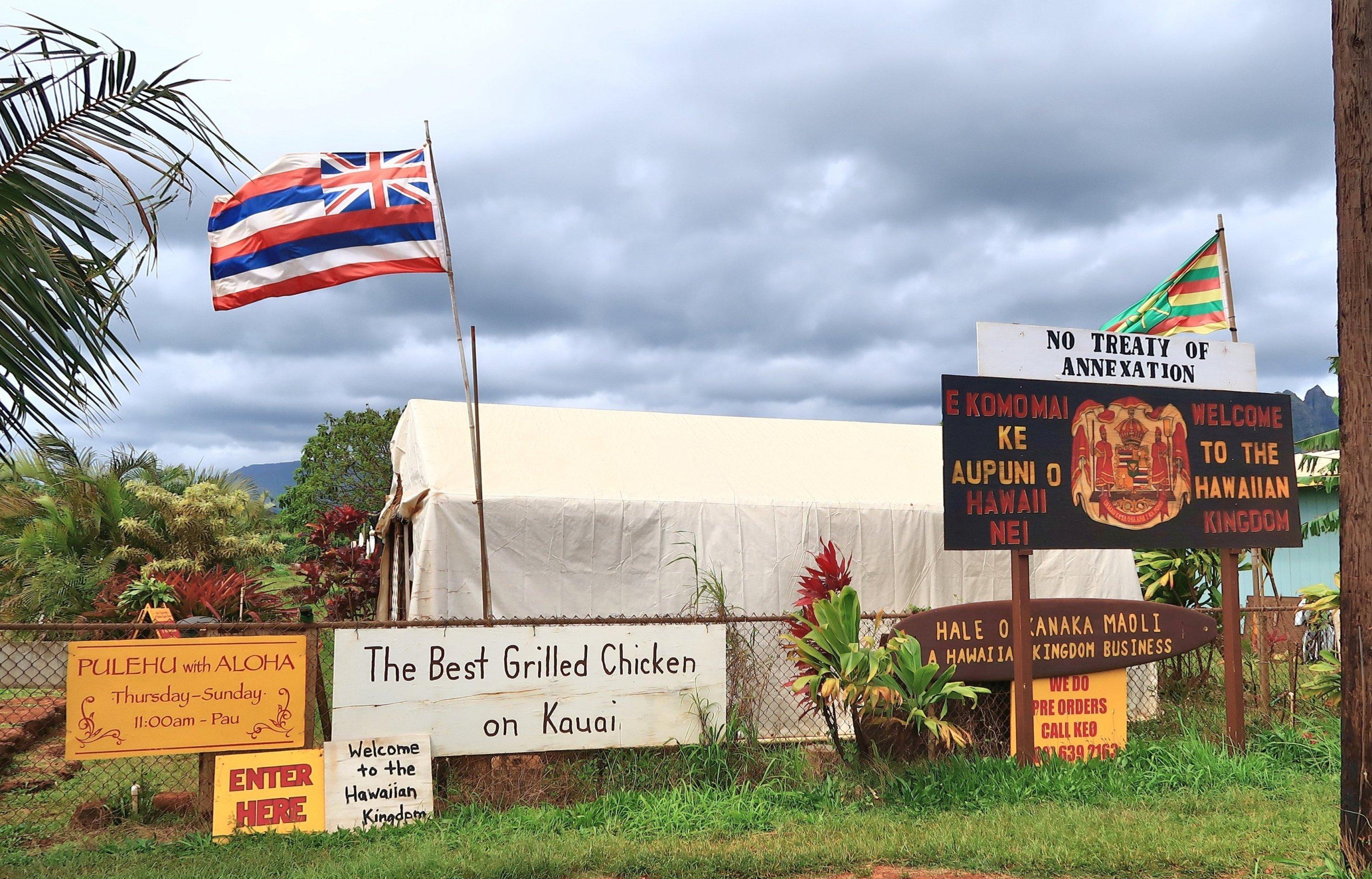 Ein Zaun mit Schildern, dahinter ein Zelt und Flaggen.