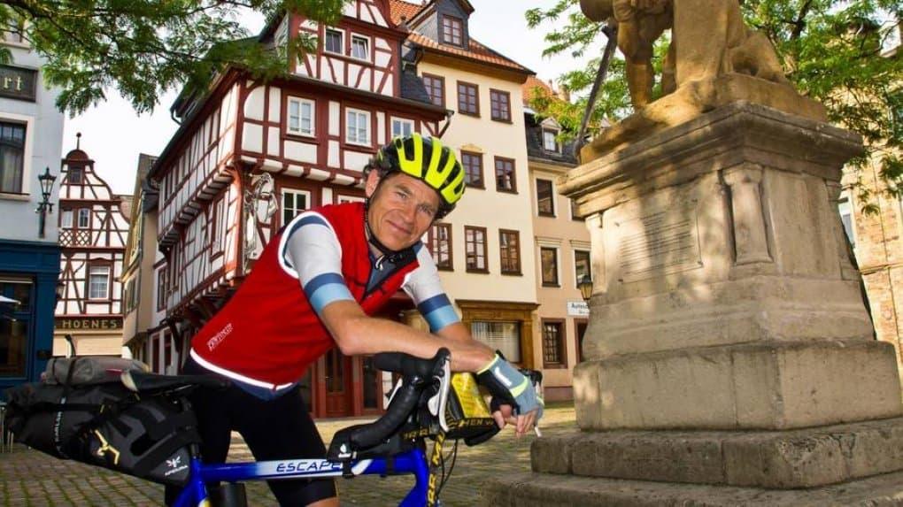 Martin C Roos, gestützt auf den Rennradlenker vor einem Steindenkmal.