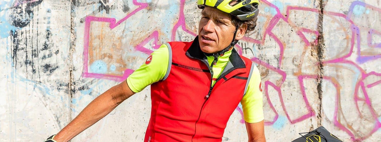 Porträt Martin C. Roos mit Radhelm, die Mauer mit Graffiti im Hintergrund.