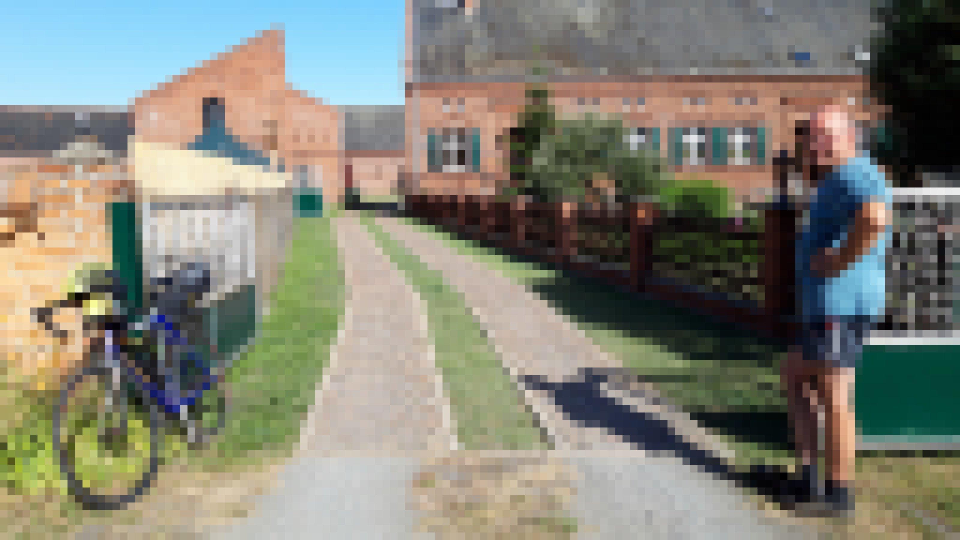 Rechts von der akkurat gepflasterten Einfahrt der kurzhosige Pey, links das Vehikel des RadelndenReporters.