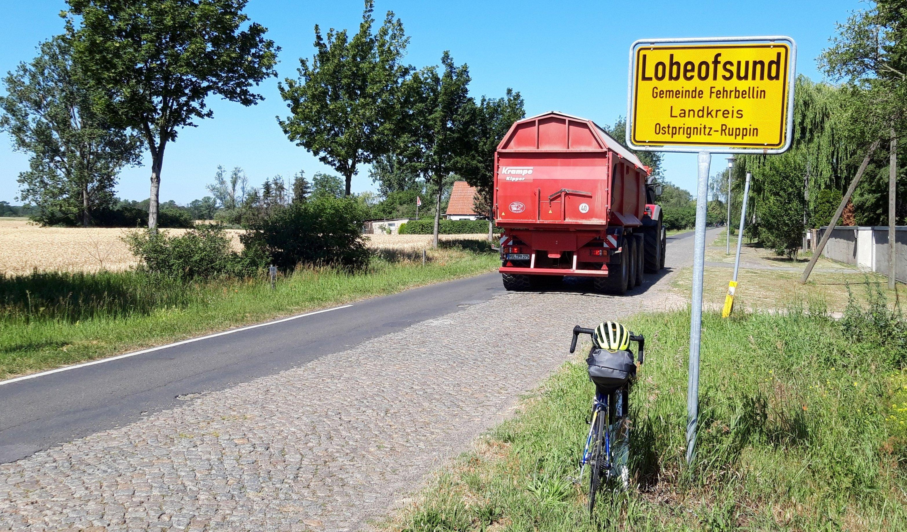 Das Rad lehnt am Ortsschild von Lobeofsund, auf der Kopfsteinpflasterstraße ist nur eine Spur asfaltiert.
