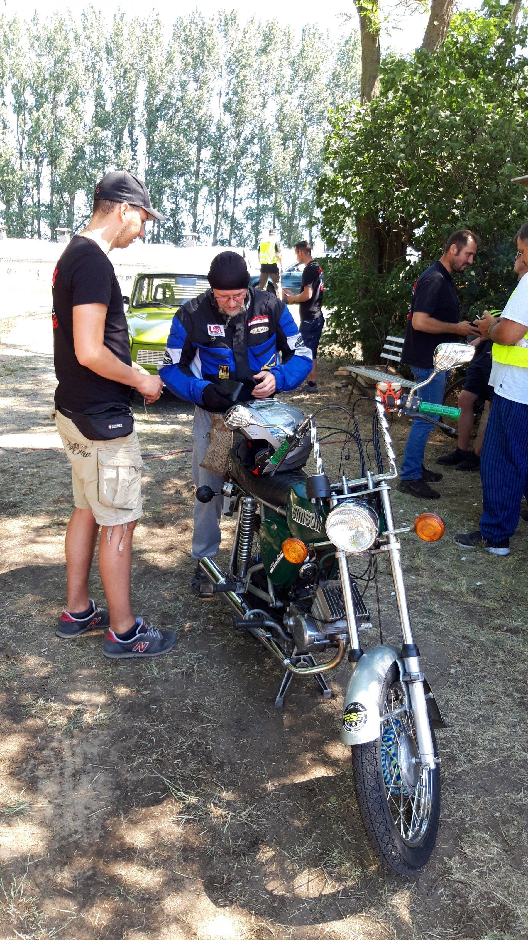 Ein Baseballbemützter kassiert von einem Motorradfahrer das Eintrittsgeld.