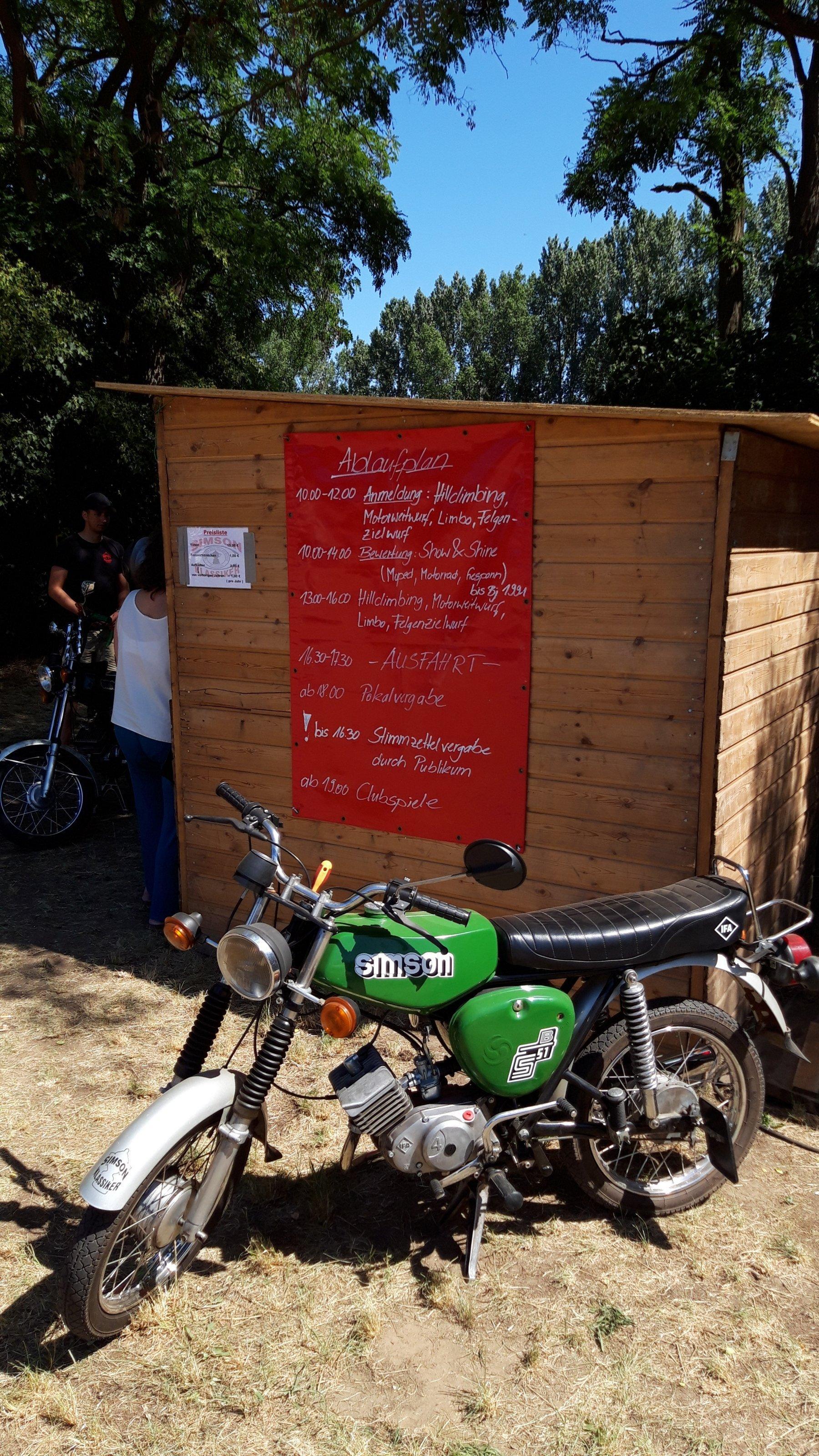 Per Hand geschrieben stehen die Veranstaltungsdetails auf einer großen Tafel, davor ein Motorrad