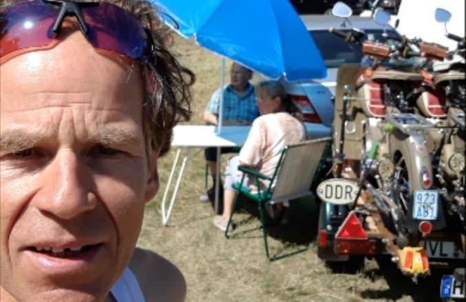 Martin C Roos im Porträtanschnitt vor Teilnehmern mit einem DDR-beschrifteten Simson.