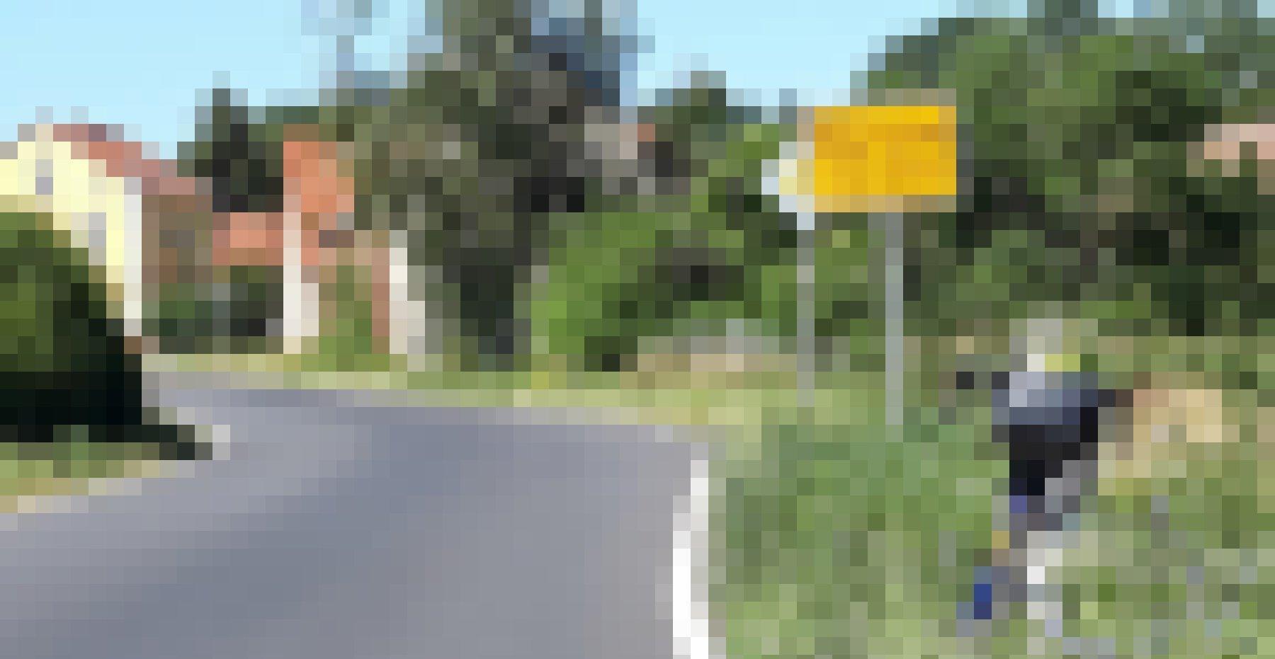 """Schild """"Warsow"""" vor Ortseinfahrt mit Häusern und Bäumen."""