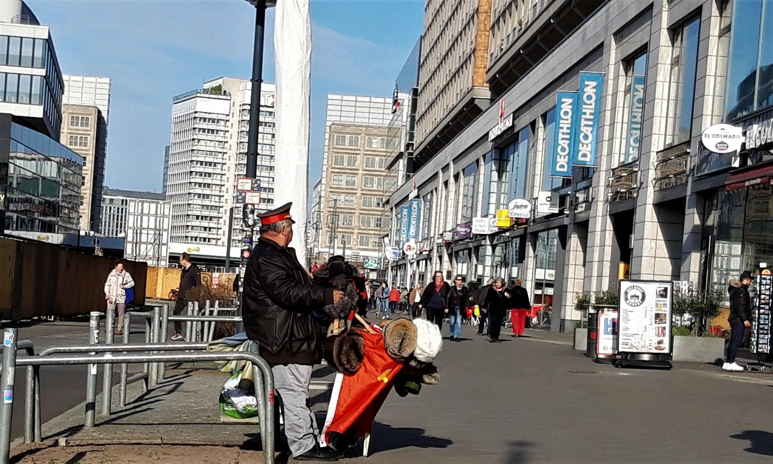 Ein untersetzter Mann hat eine Sowjet-Uniformmütze auf und verkauft Pelzmützen und andere Sowjet-Souvenirs