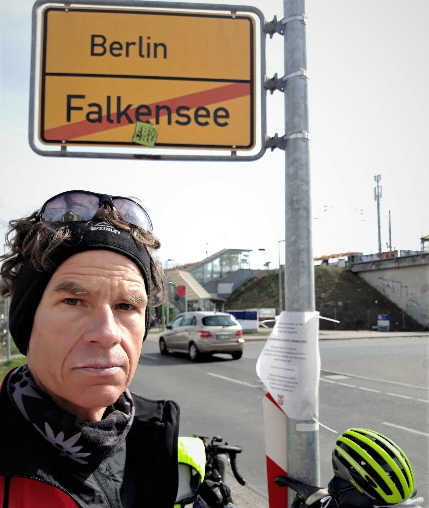 Ein abgekämpft wirkender Martin C. Roos macht ein Selfie am Ortsschild von Berlin, an dessen Pfahl ein offiziell wirkender Aushang befestigt ist. Im Hintergrund zu sehen: Der Bahnhof Albrechtshof.