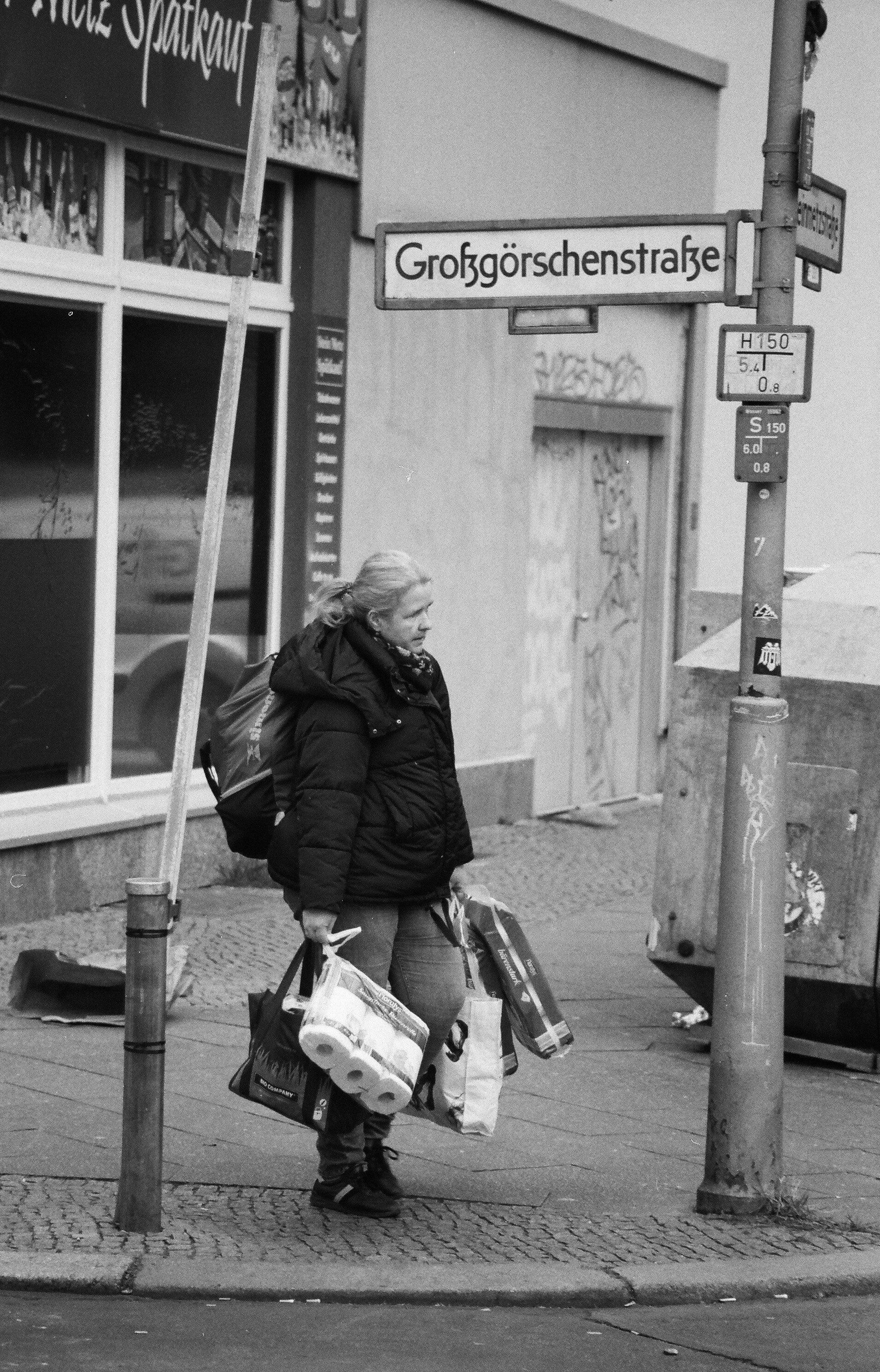 Eine voll bepackte Frau trägt zusätzlich zu den Einkaufstaschen eine Packung Toilettenpapier an jeder Hand.