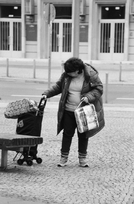 Eine Frau hat rechts einen Rollwagen an der Hand und trägt links eine Packung Toilettenpapier.