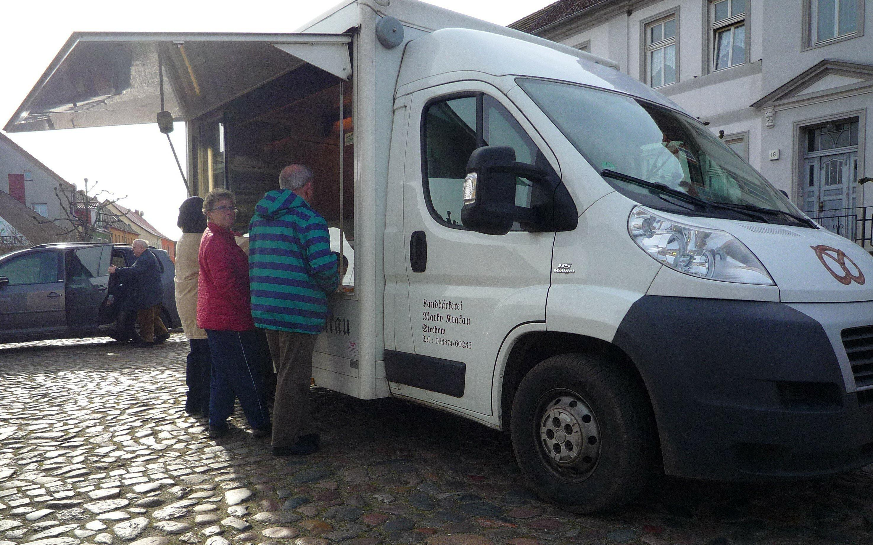 Vor einem Brotverkaufswagen stehen drei ältere Menschen dichgedrängt an der Theke.