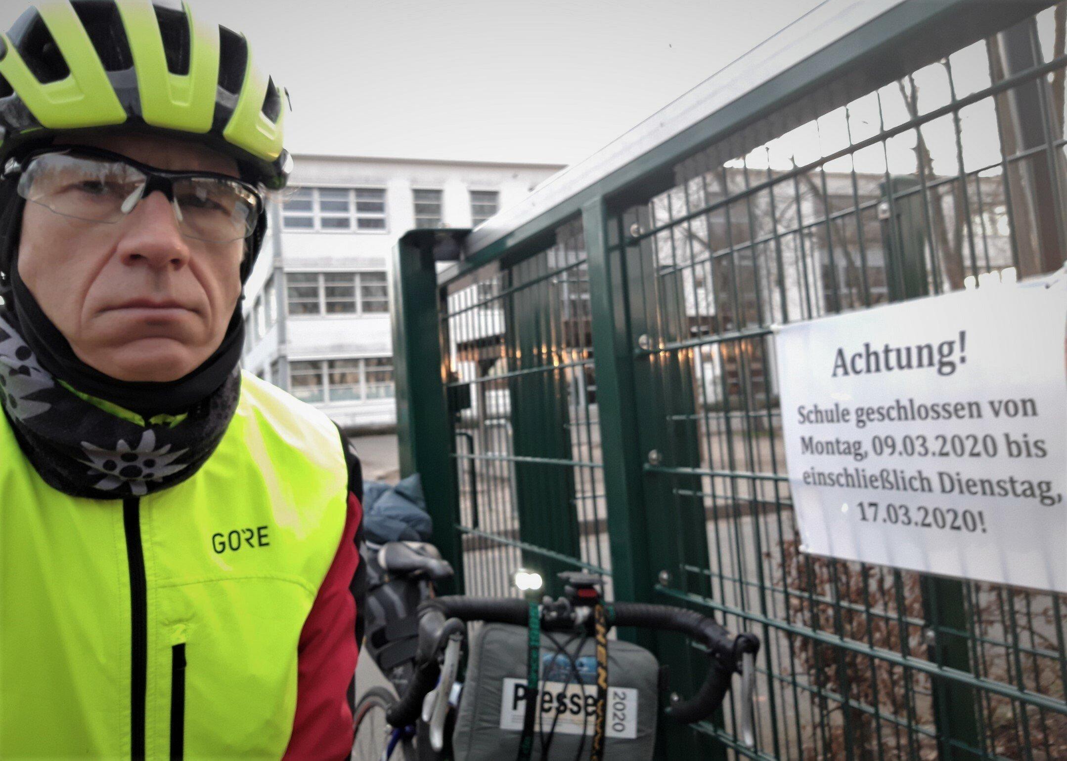 """Martin C Roos vor dem Schulgebäude. Am Zaun hängt das Schild mit der Aufschrift """"Achtung! Schule geschlossen von Montag 9.3.2020bis einschließlich Dienstag 17.3.2020!"""""""