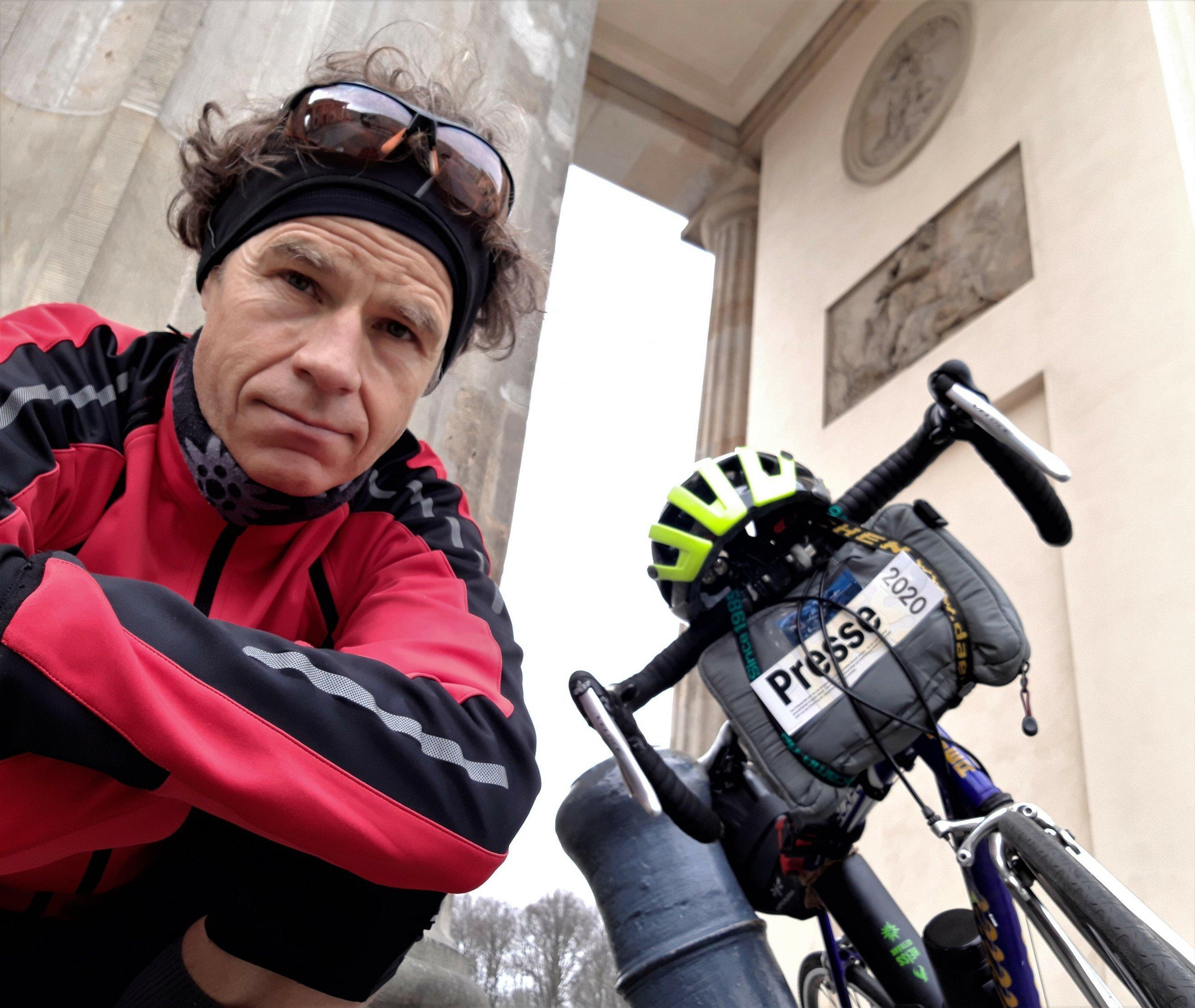 Martin C. Roos schaut in die Kamera, im Hintergrund ein Teil seines Rads und des Brandenburger Tors.