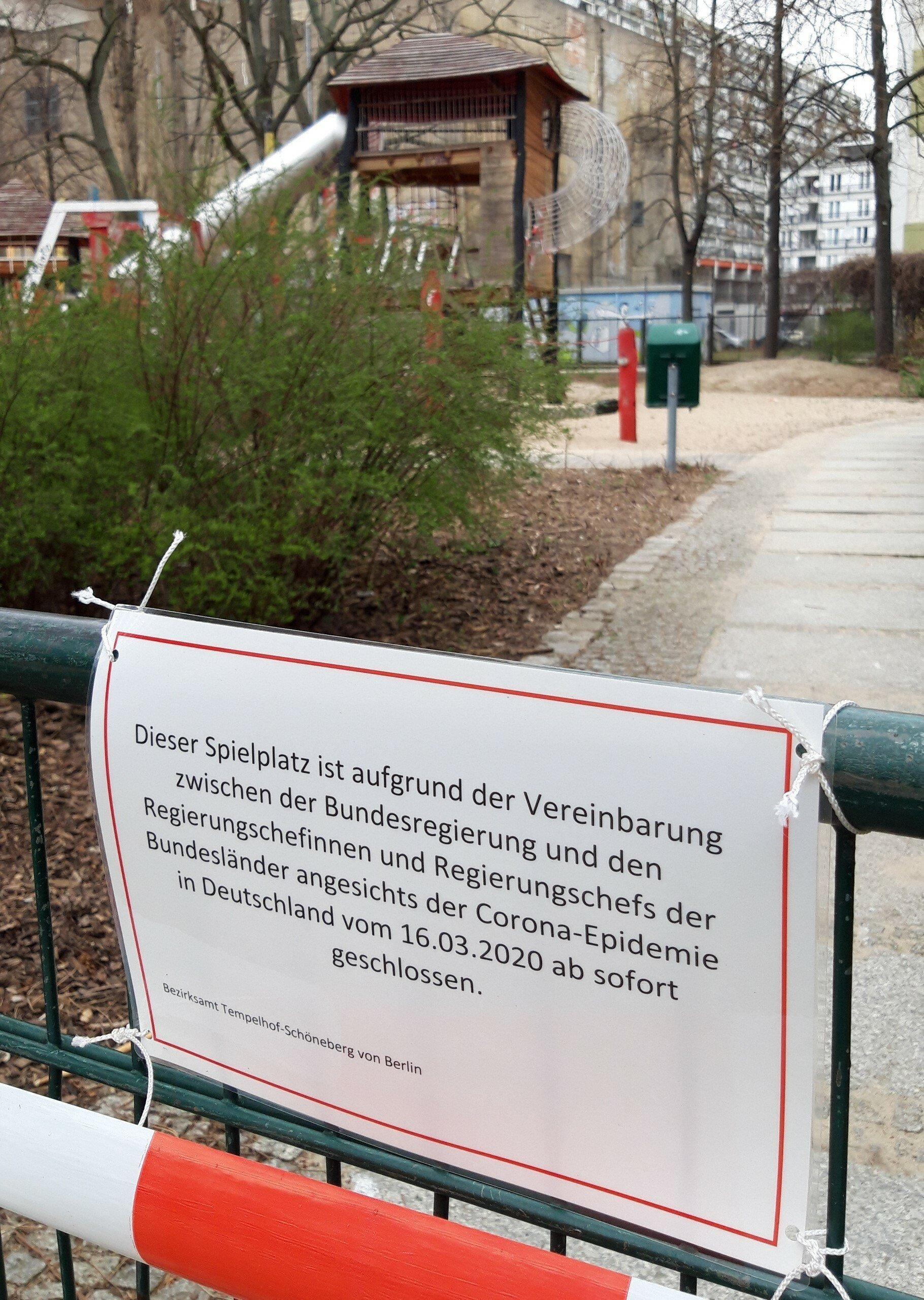 """Am verschlossenen Gitter eines Platzes hängt das Schild: """"Dieser Spielplatz ist … ab sofort geschlossen."""""""