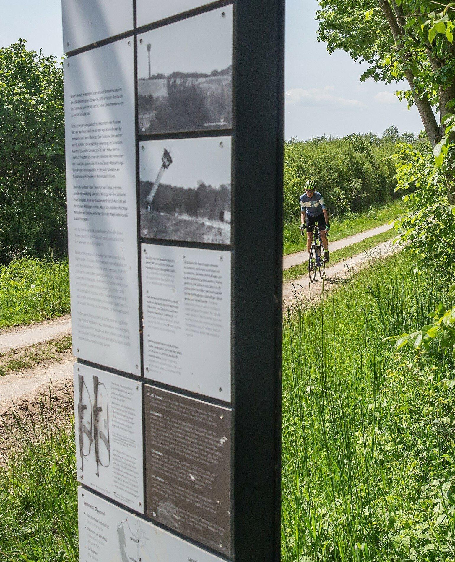 Martin C Roos fährt mit dem Rennrad auf einem alten Kolonnenweg, an dem – im Bildvordergrund – eine Schautafel des Museums zu sehen ist.