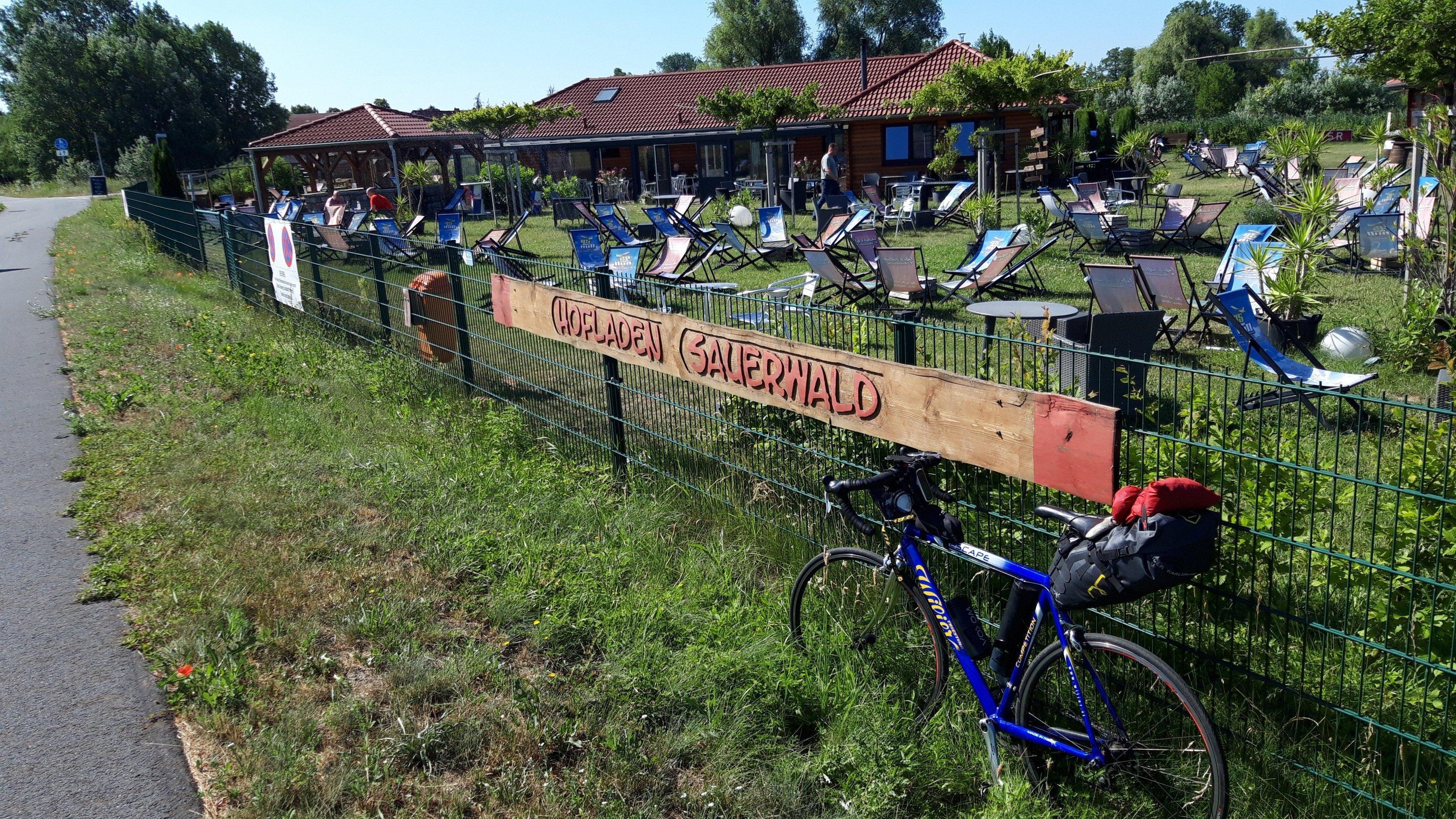 Das Rad des RadelndenReporters lehnt am Zaun, hinter dem sich Liegestühle auf einer Wiese verteilen.