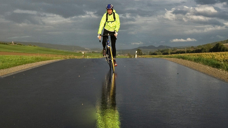 Rennrad-Reporter Martin C Roos fährt auf regennasser Fahrbahn direkt auf die Kamera zu. Die Sonne scheint bereits wieder, am Horizont dräuen dunkle Wolken