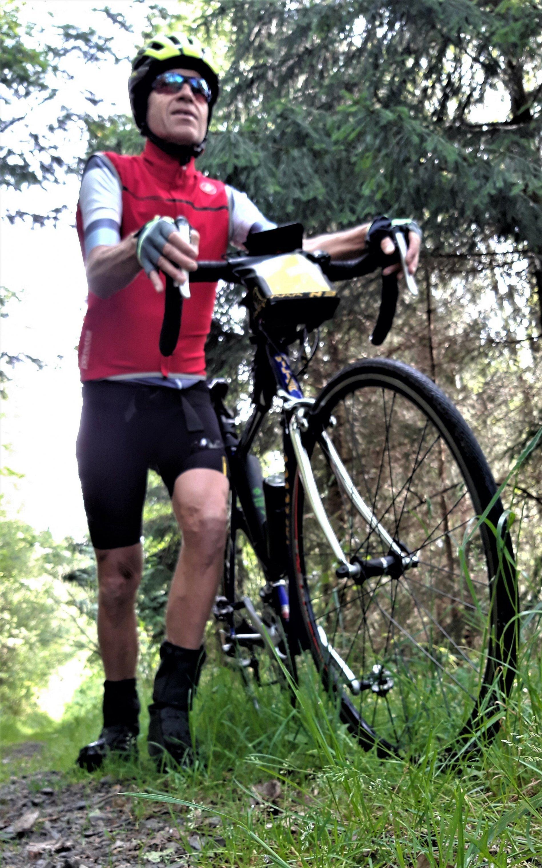 Martin C. Roos schiebt sein Rennrad durch dichten Wald.
