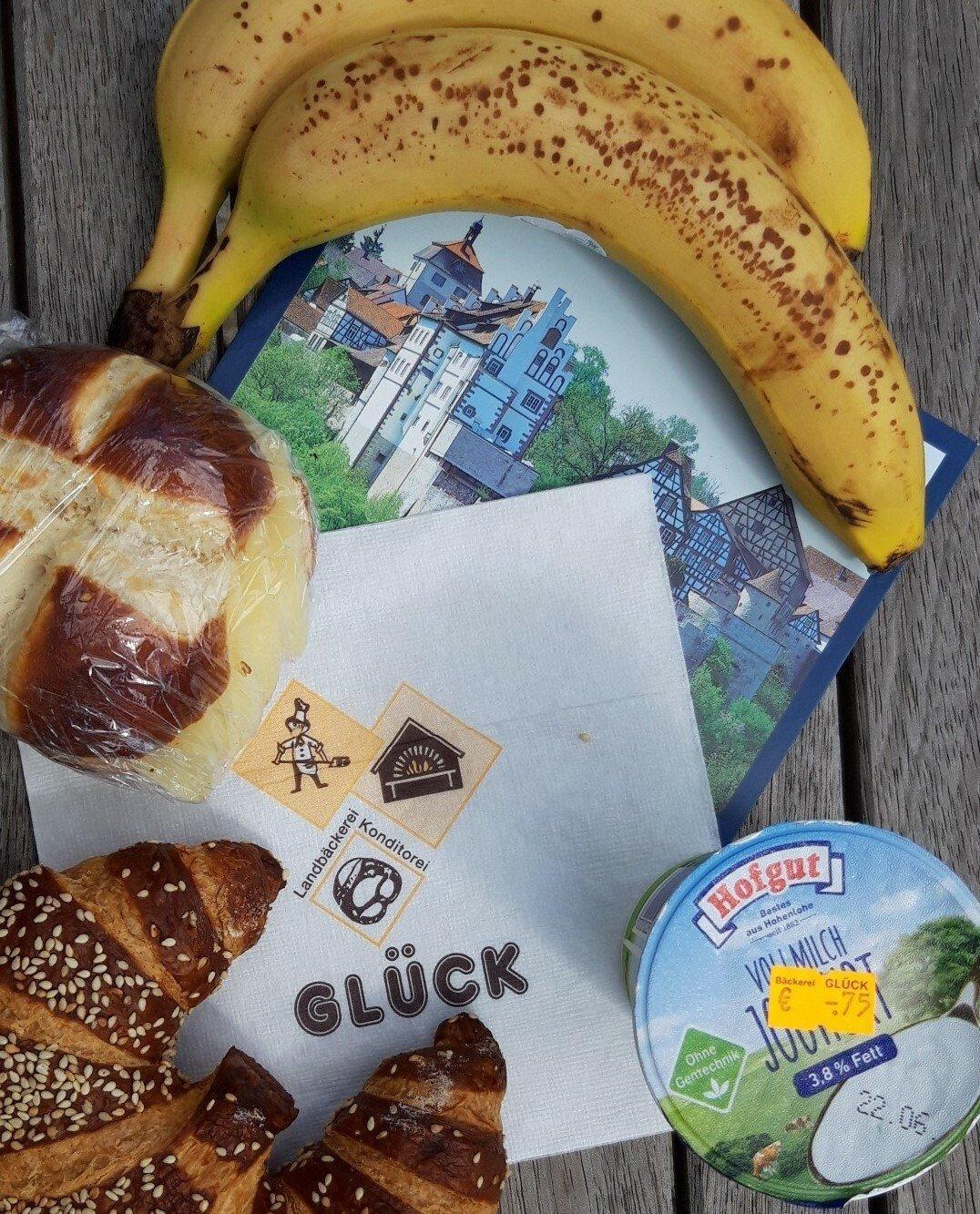 Stillleben auf einer Parkbank mit Banane, Joghurt, Laugenbrötchen.