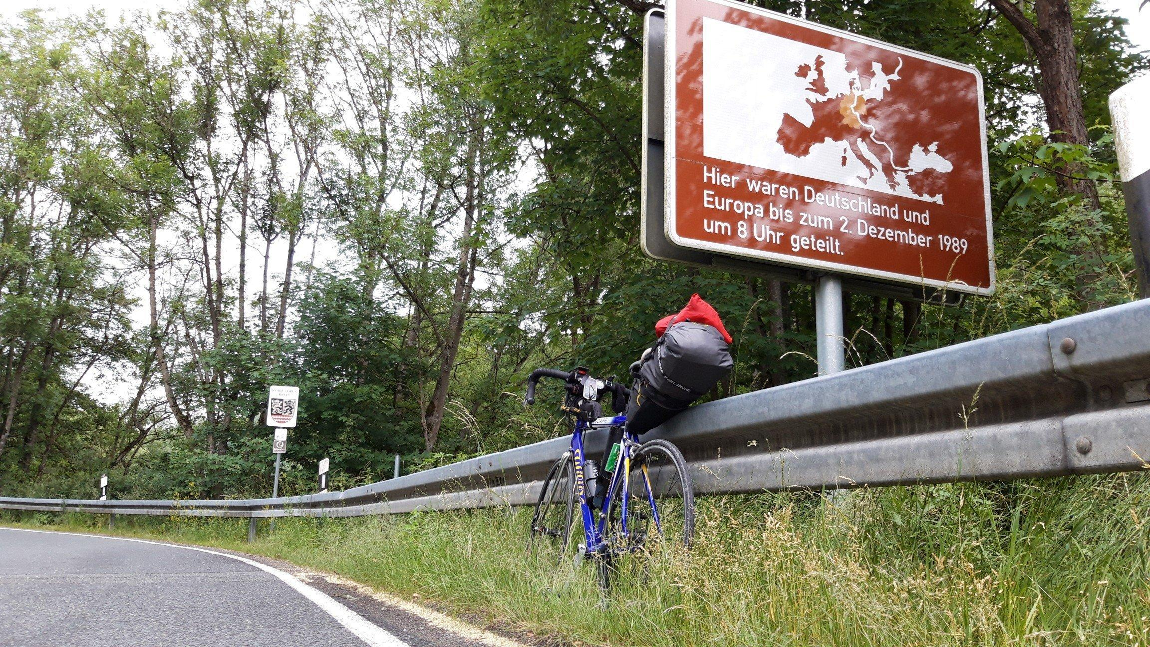 """An der Grenze zu Thüringen steht das Schild """"Hier waren Deutschland und Europa bis zum 2. Dezember 1989um 8Uhr geteilt""""."""