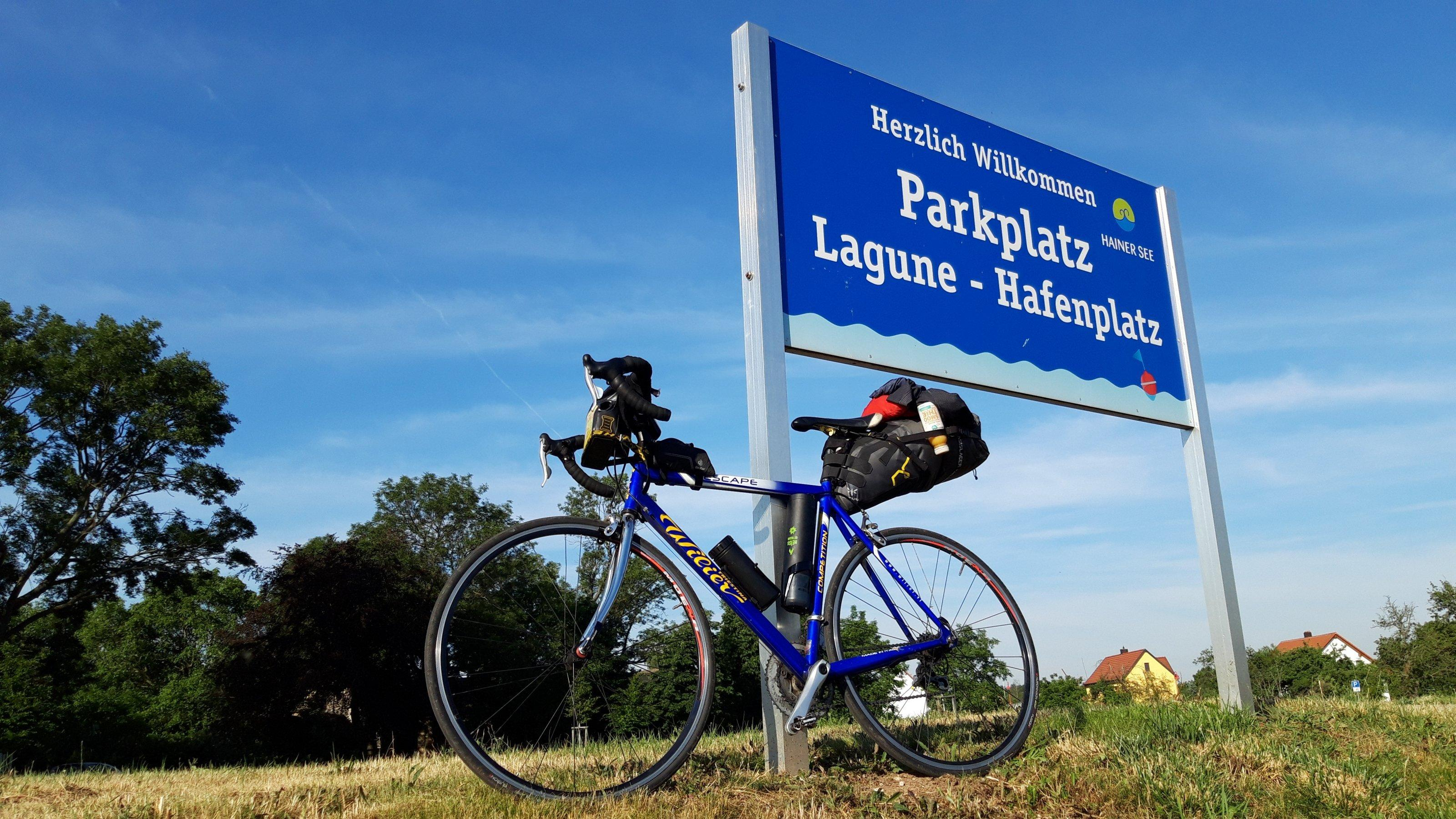Das Rad lehnt an einem Schild mit der Aufrschrift Parkplatz Lagune – Hafenplatz Hainer See.