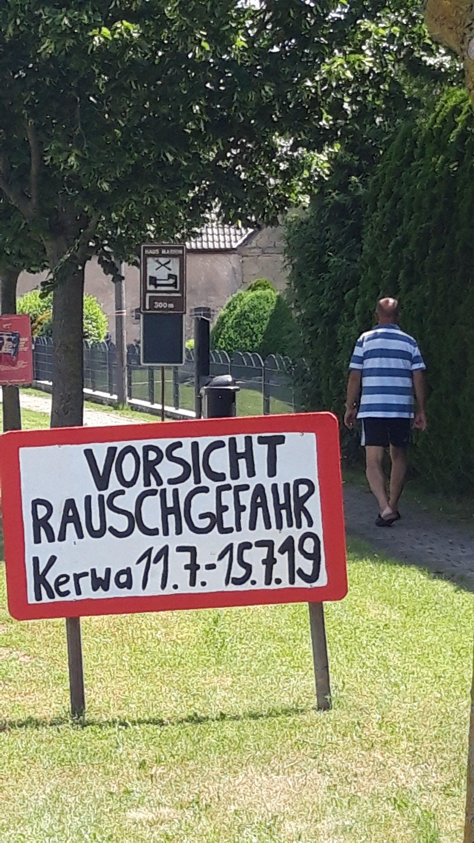 """Auf dem Grünstreifen neben der Dorfstraße steht """"Vorsicht Rauschgefahr – Kerwa 11.7.-15.7.19""""."""