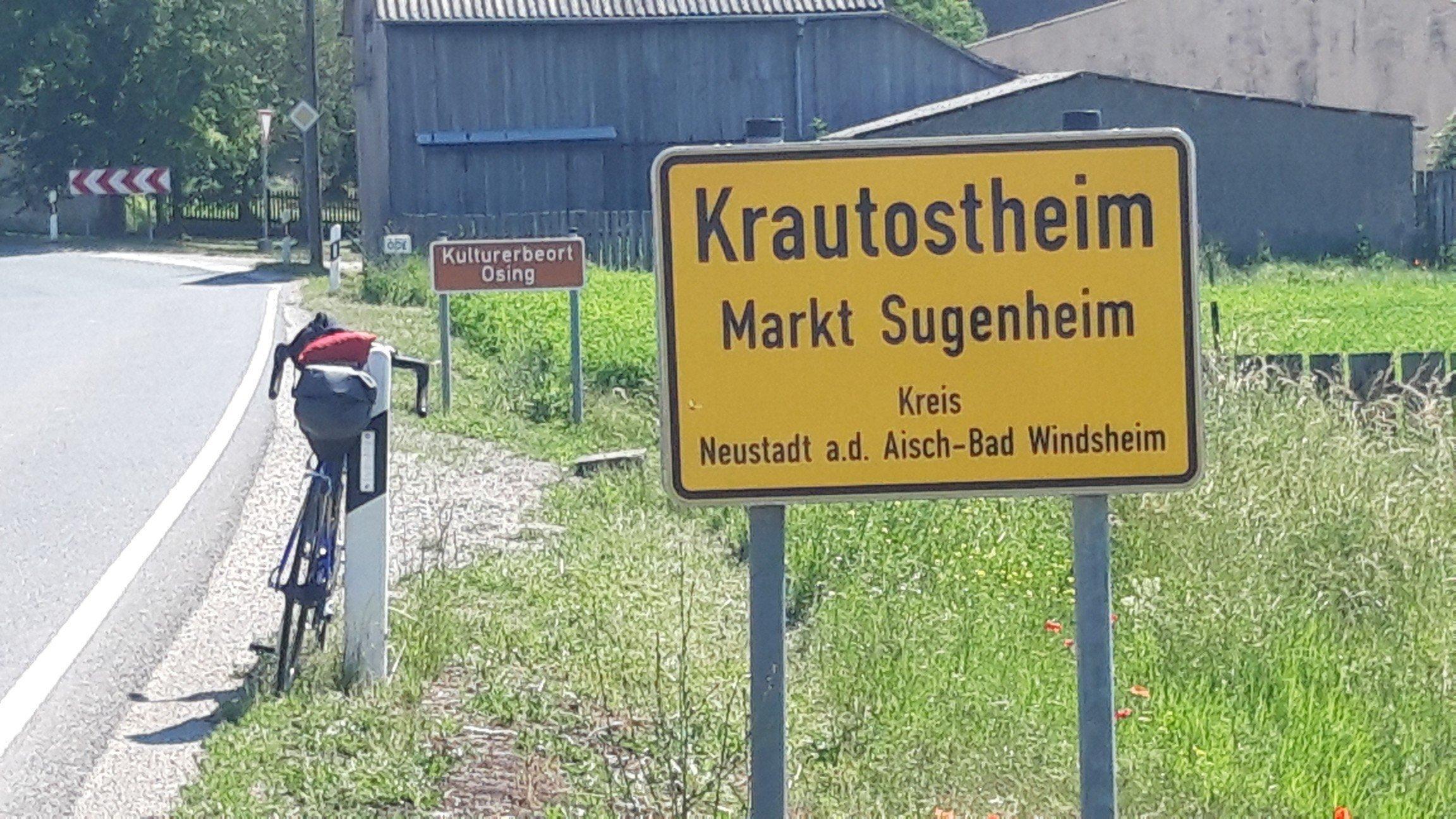 """hinter dem Ortschild von Krautostheim ist das braune """"Kulturerbe""""-Schild zu sehen sowie das Vehikel des RadelndenReporters."""