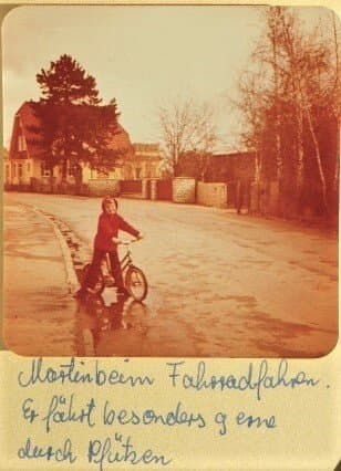 """Kleinkind Martin C Roos auf seinem Erstrad, Aufnahme im Familienalbum handschriftlich ergänzt durch den Satz """"Er fährt besonders gern durch Pfützen""""."""