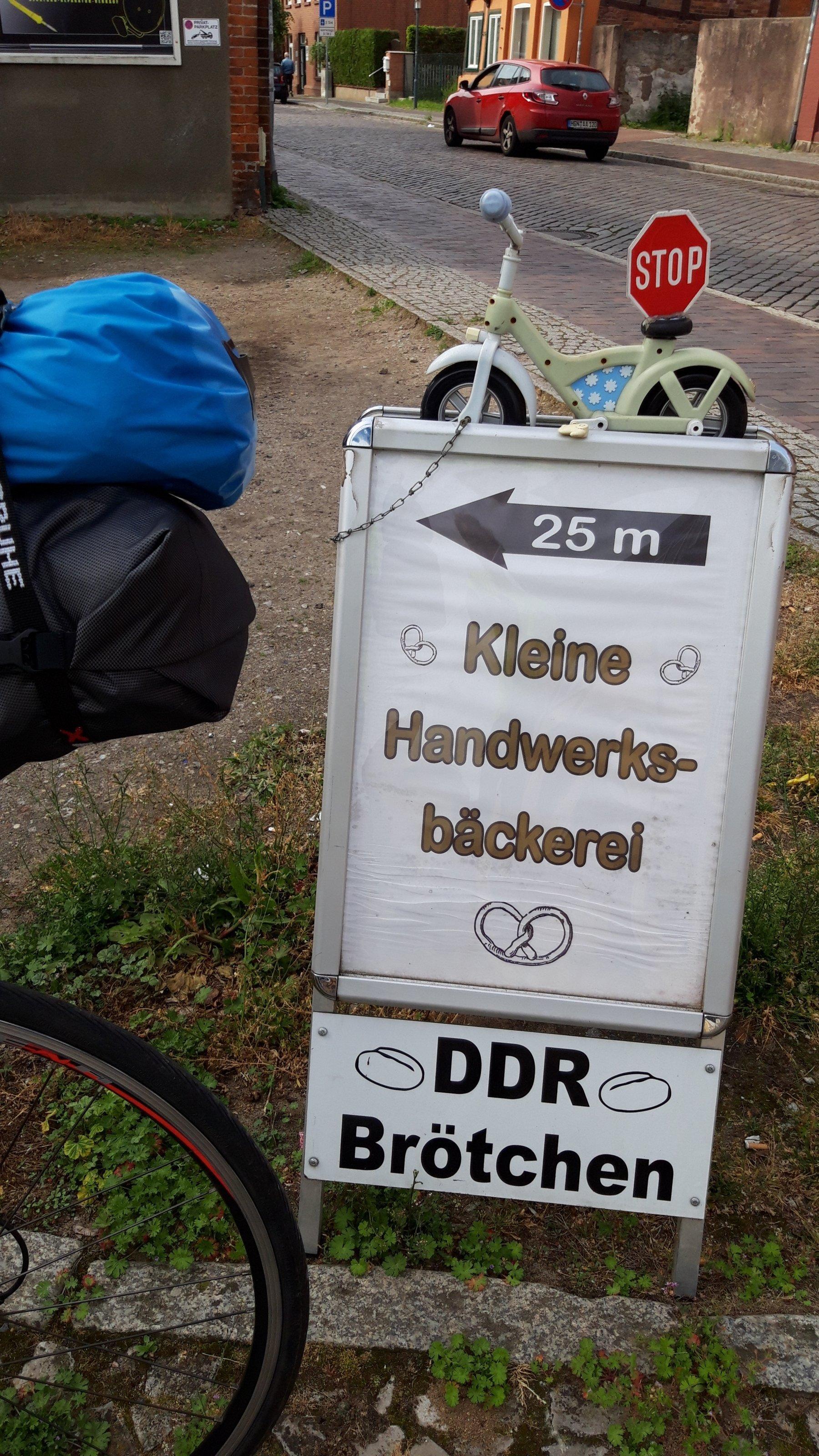 """Das Vehikel des RadelndenReporters parkt neben einem Hinweisschild, auf dem zu lesen ist """"DDR-Brötchen, Kleine Handwerksbäckerei, 25Meter""""."""