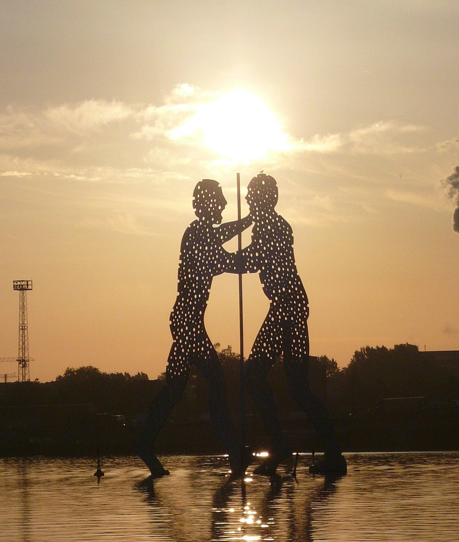 """Lochplatten-Skulpturen des """"Molecule Man"""" im Gegenlicht der untergehenden Sonne. Von den drei Skulpturen sind aufgrund des Aufnahmewinkels nur zwei zu sehen."""