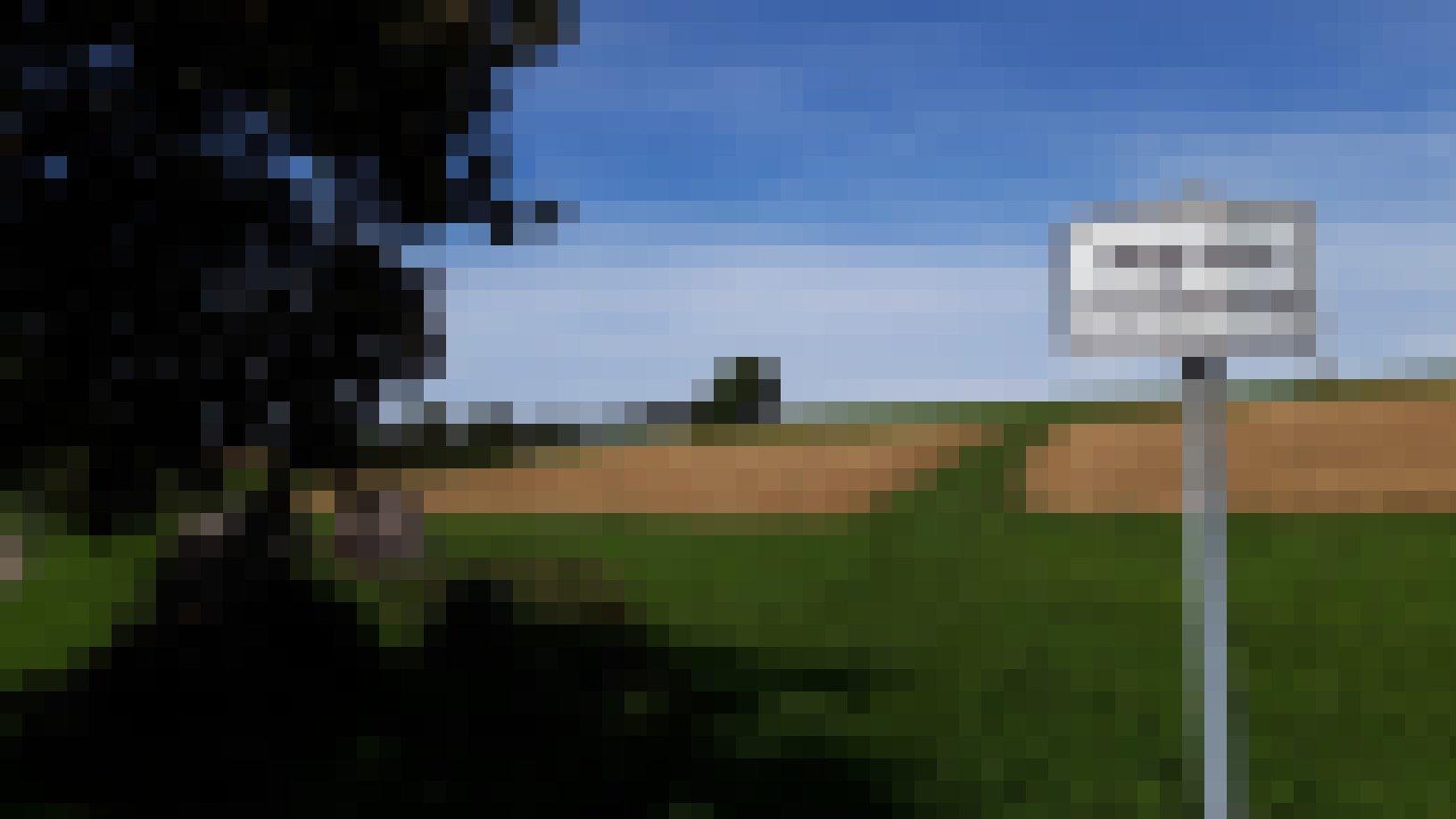 """Vor einer durch zwei Feldflächen geteilten grünen Wiese steht das Schild """"Weg ohne Fortsetzung""""."""