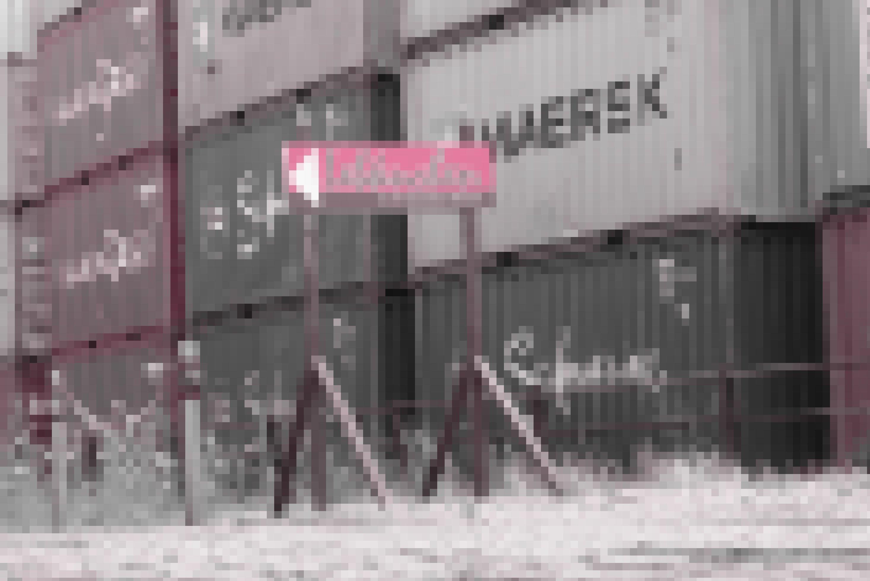 Hinweisschild einer Bremer Lebkuchen-Manufaktur vor dem Hintergrund gestapelter Schiffscontainer.