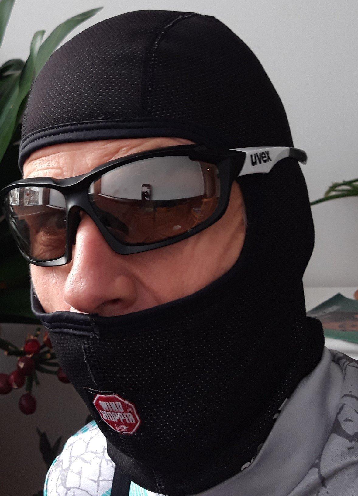 Bebrillter Radfahrer mit Sturmhaube über dem Kopf