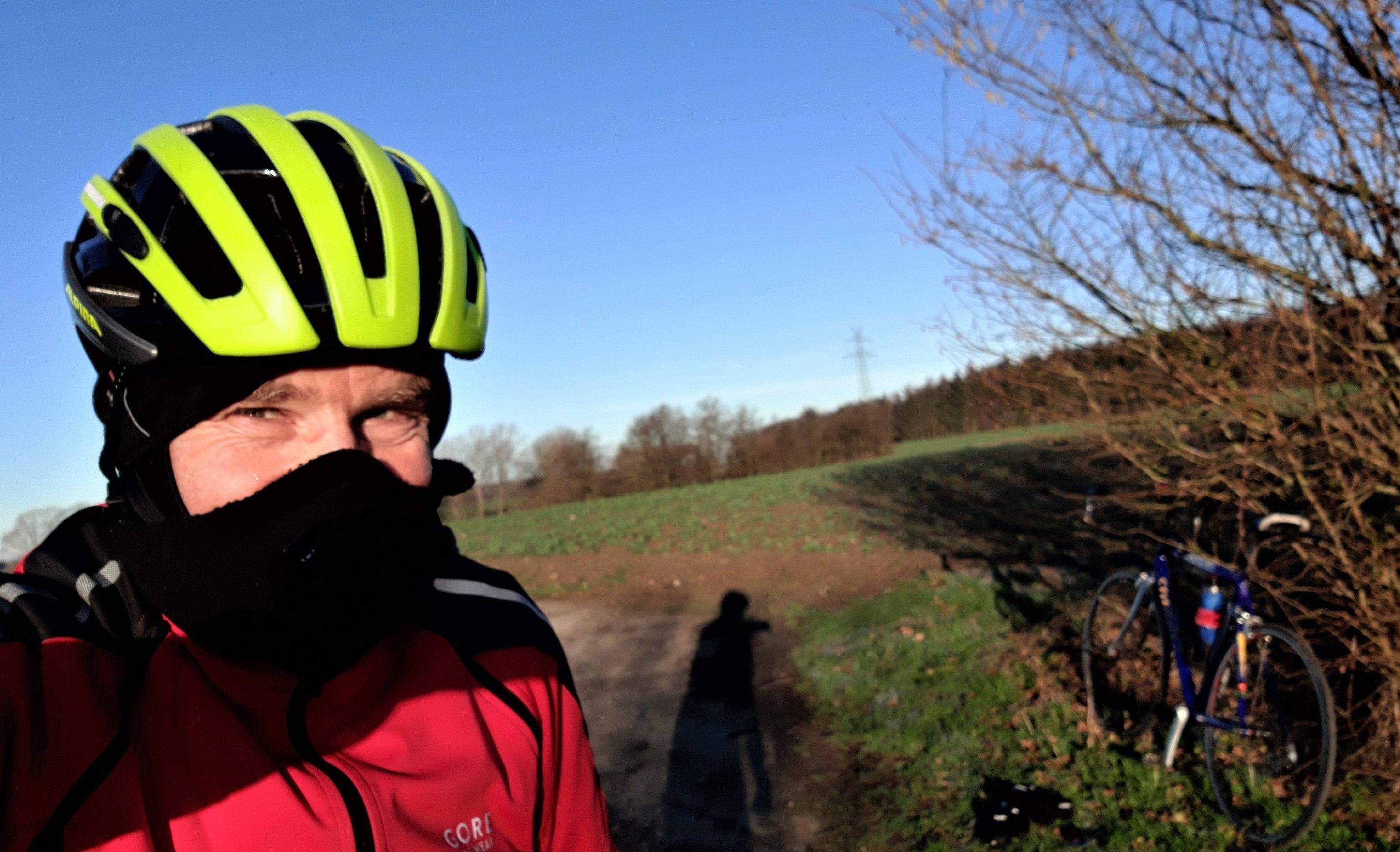 Radfahrer mit Helm, Sturmhaube und Nasenschutz vor Winterlandschaft.