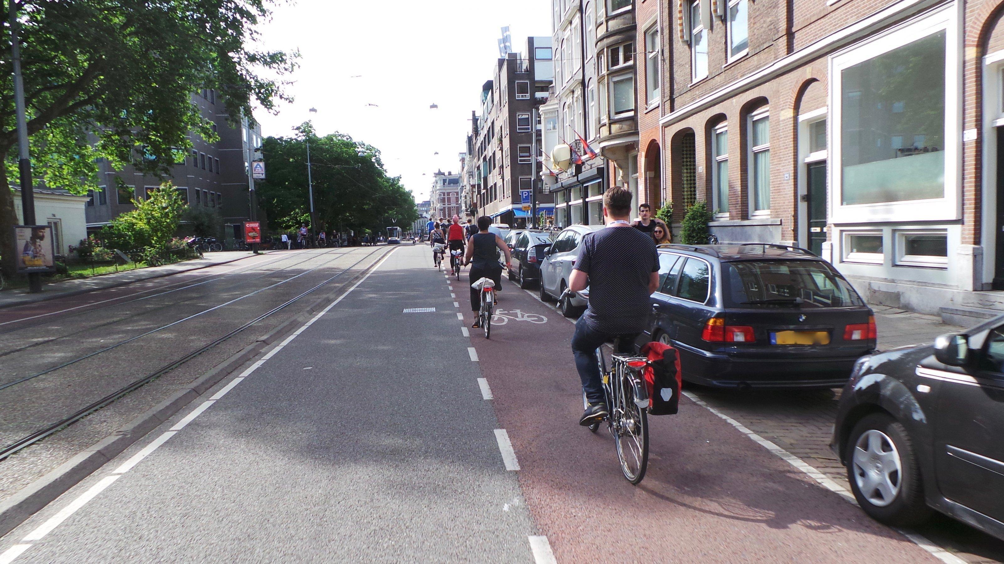 Blick auf eine Straße in Amsterdam, an deren rechter Seite Autos parken. Daneben fahren Radfahrer auf einer roten Radspur vorbei.