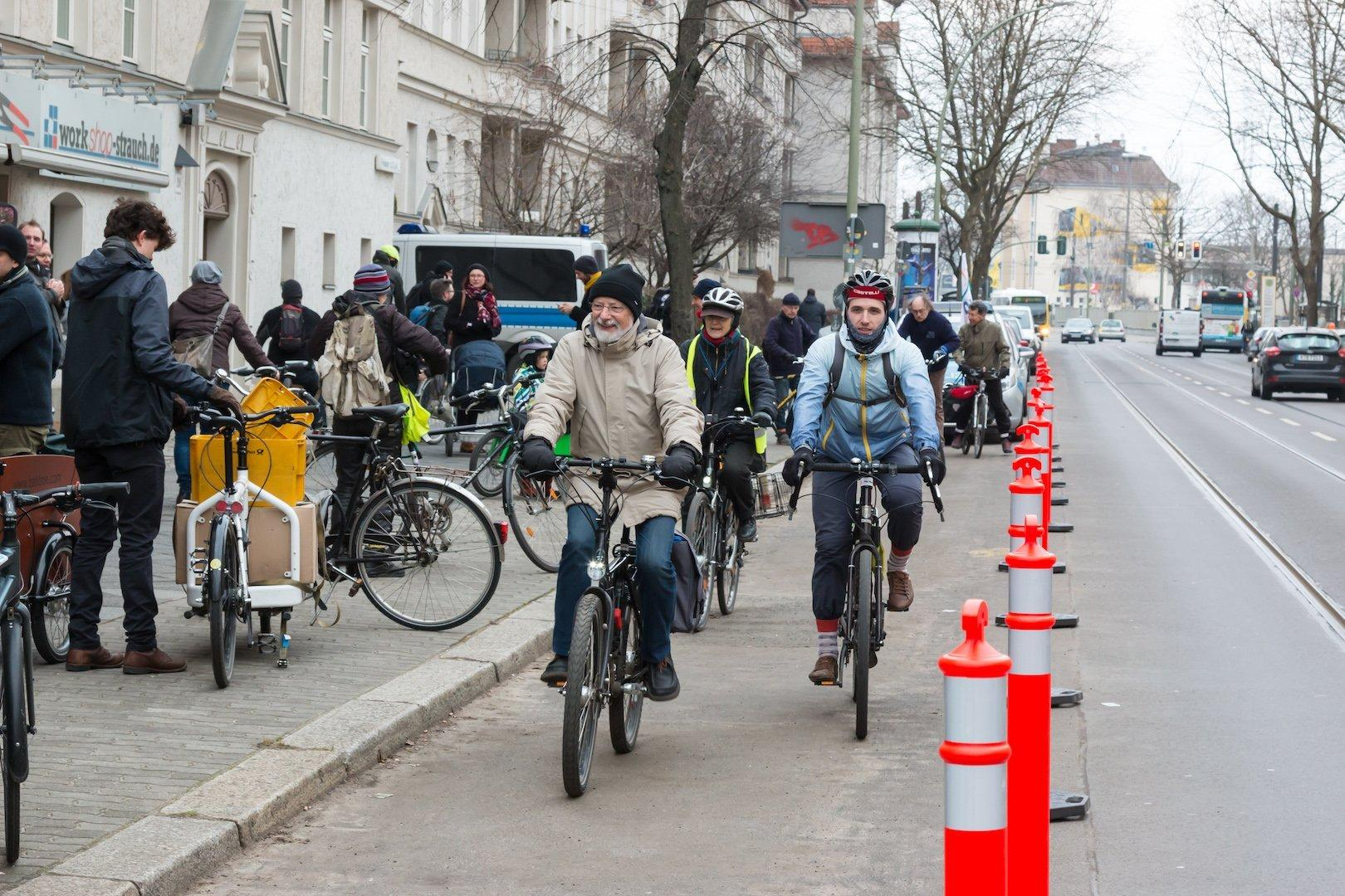 Mehrere Radfahrer fahren in Richtung Kamera auf einer gesicherten Spur. Auf dem Bürgersteig stehen weitere Menschen mit ihren Fahrrädern.