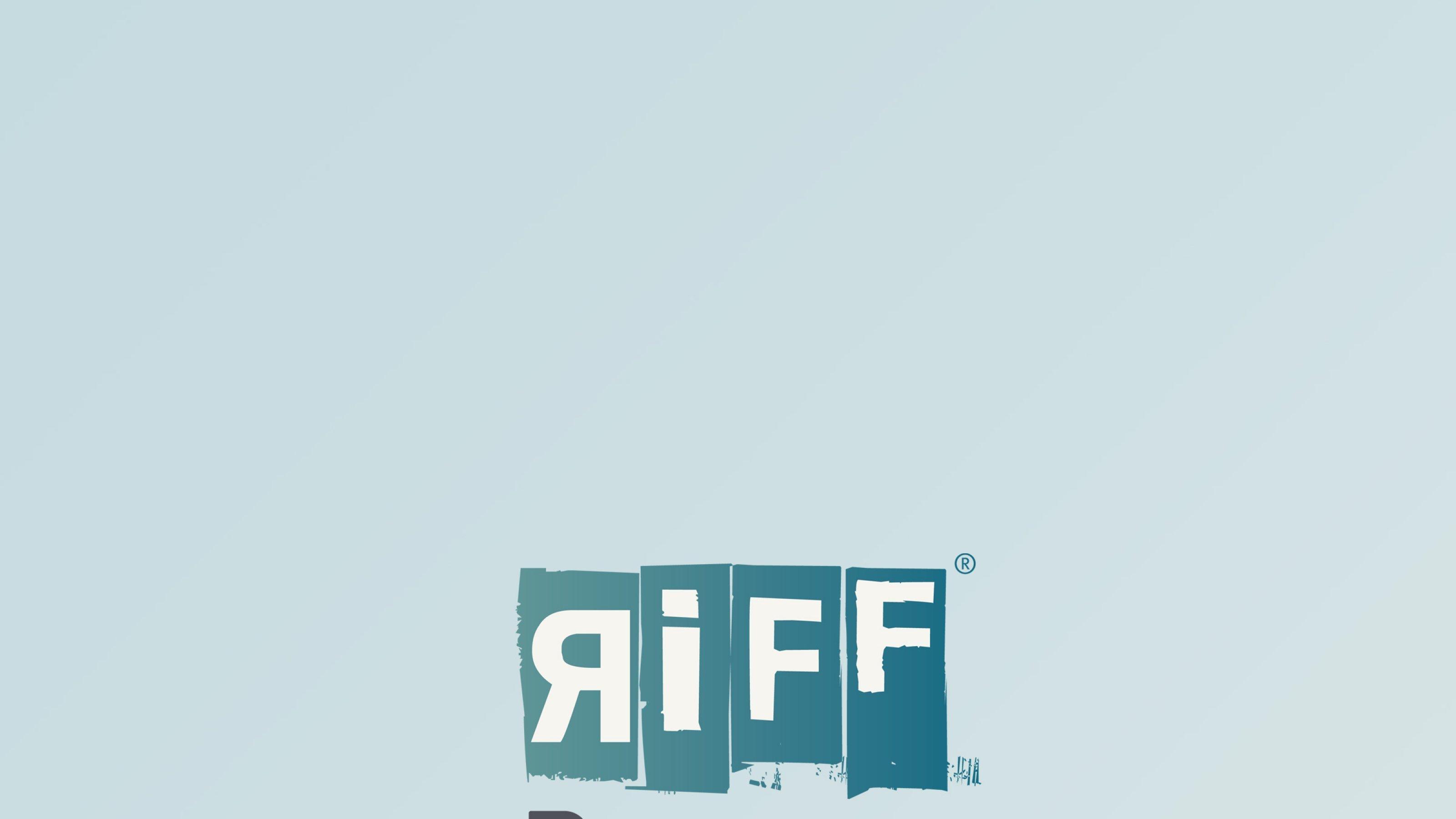 Mann blickt vom rechten Bildrand auf den Betrachter. Im unscharfen Hintergrund fährt ein Schiff auf dem Fluss Rhein unter grau bewölktem Himmel.