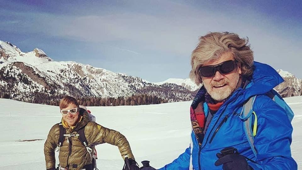 Vater und Sohn auf einem verschneiten Berghang in Skitourenausrüstung.