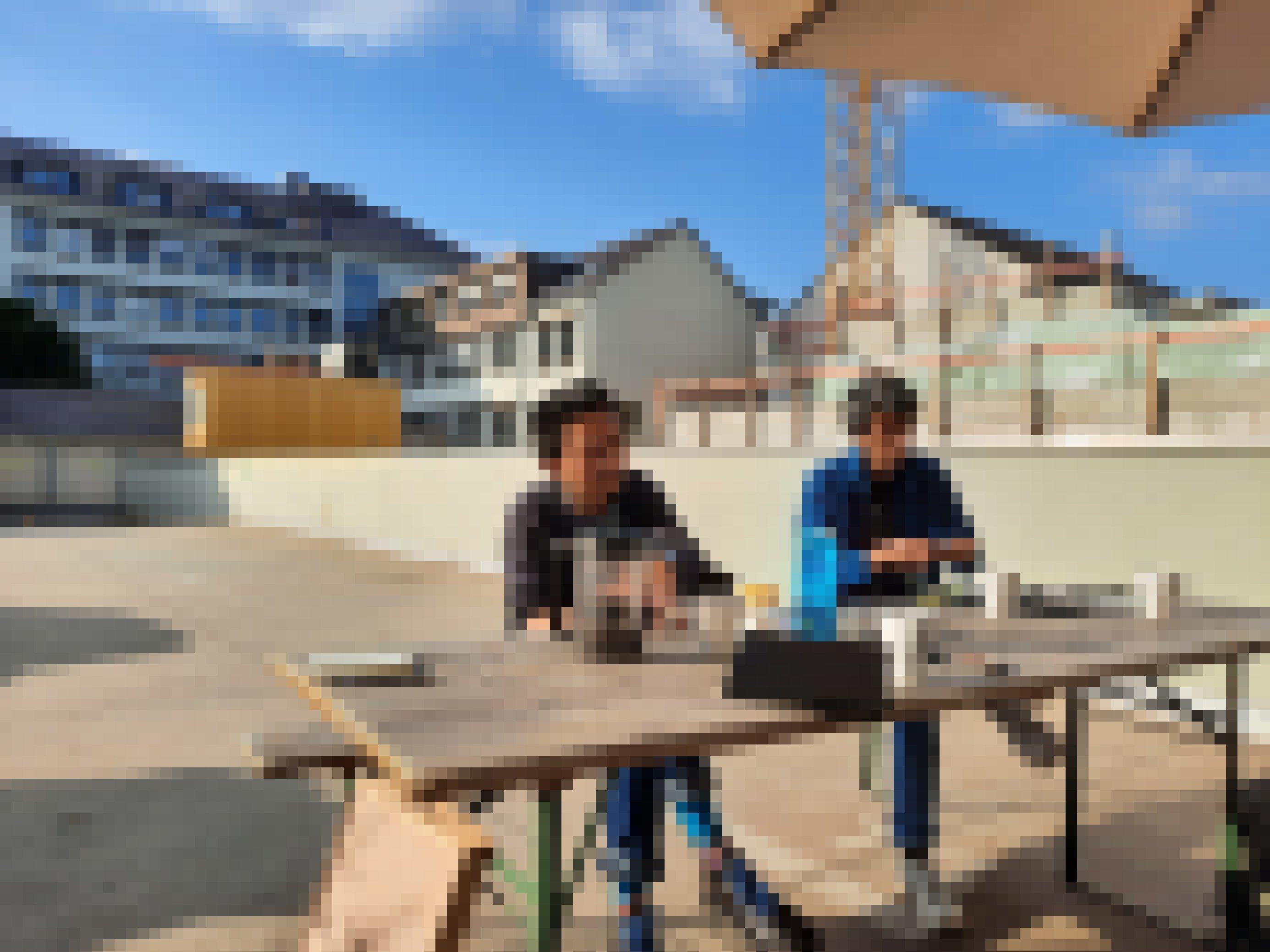 Reza Afisina und Iswanto Hartono sitzen bei schönem Wetter an einem Biertisch auf dem Parkdeck des ruruHauses in Kassel.