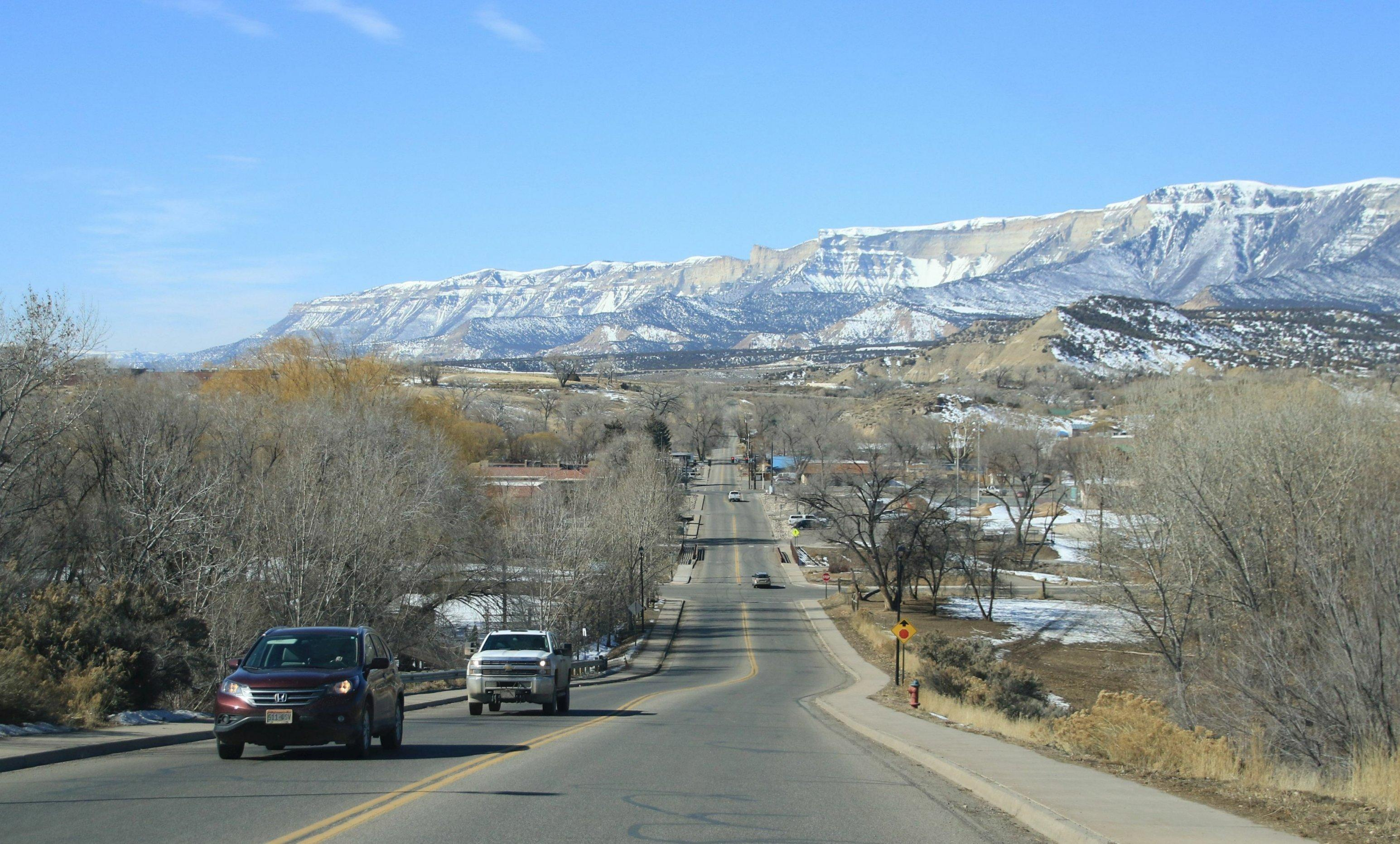 Eine hügelige Straße. Im Hintergrund schneebedeckte Berge.