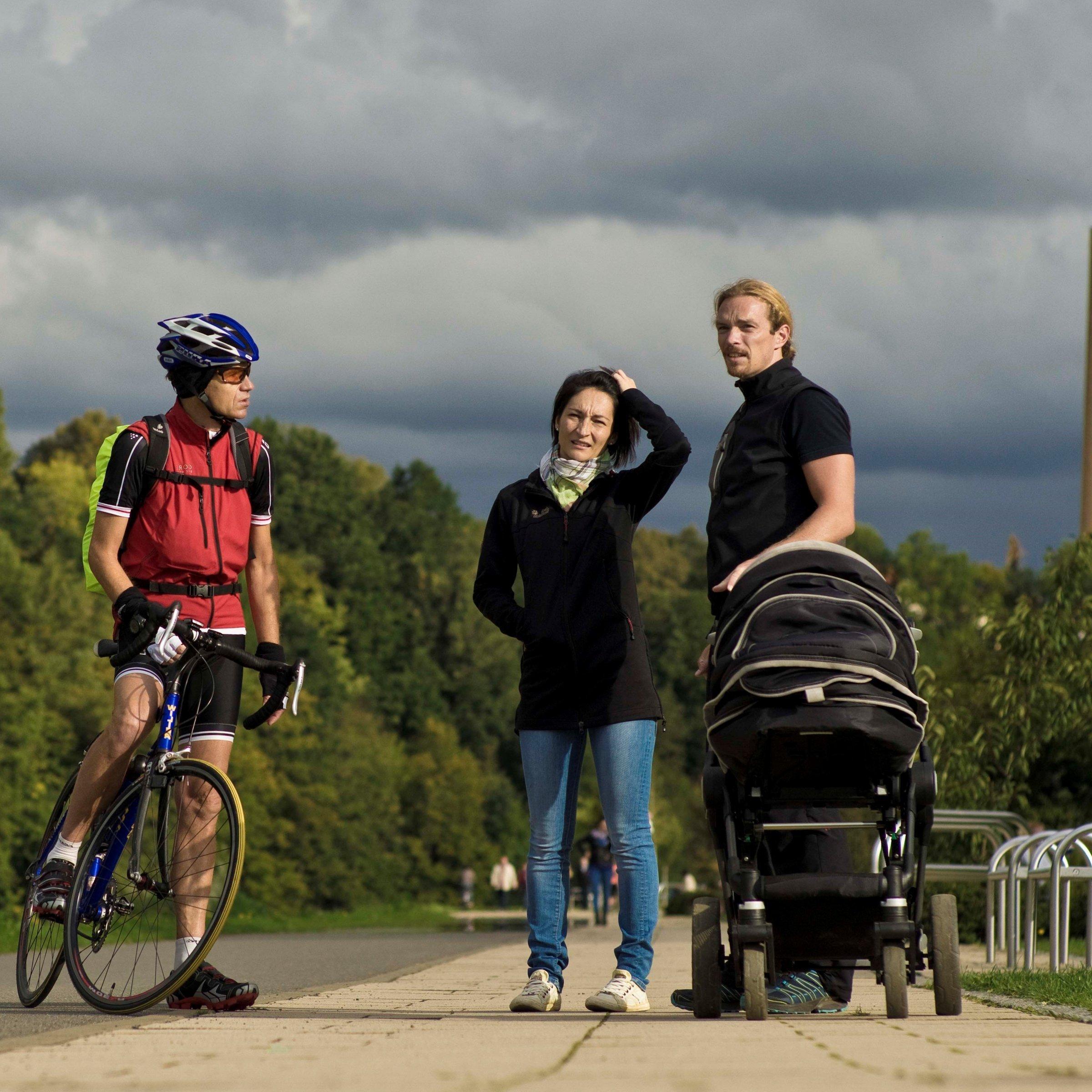 Der Reporter auf dem Rennrad im Gespräch mit einem Paar aus Sachsen, das einen Kinderwagen schiebt.