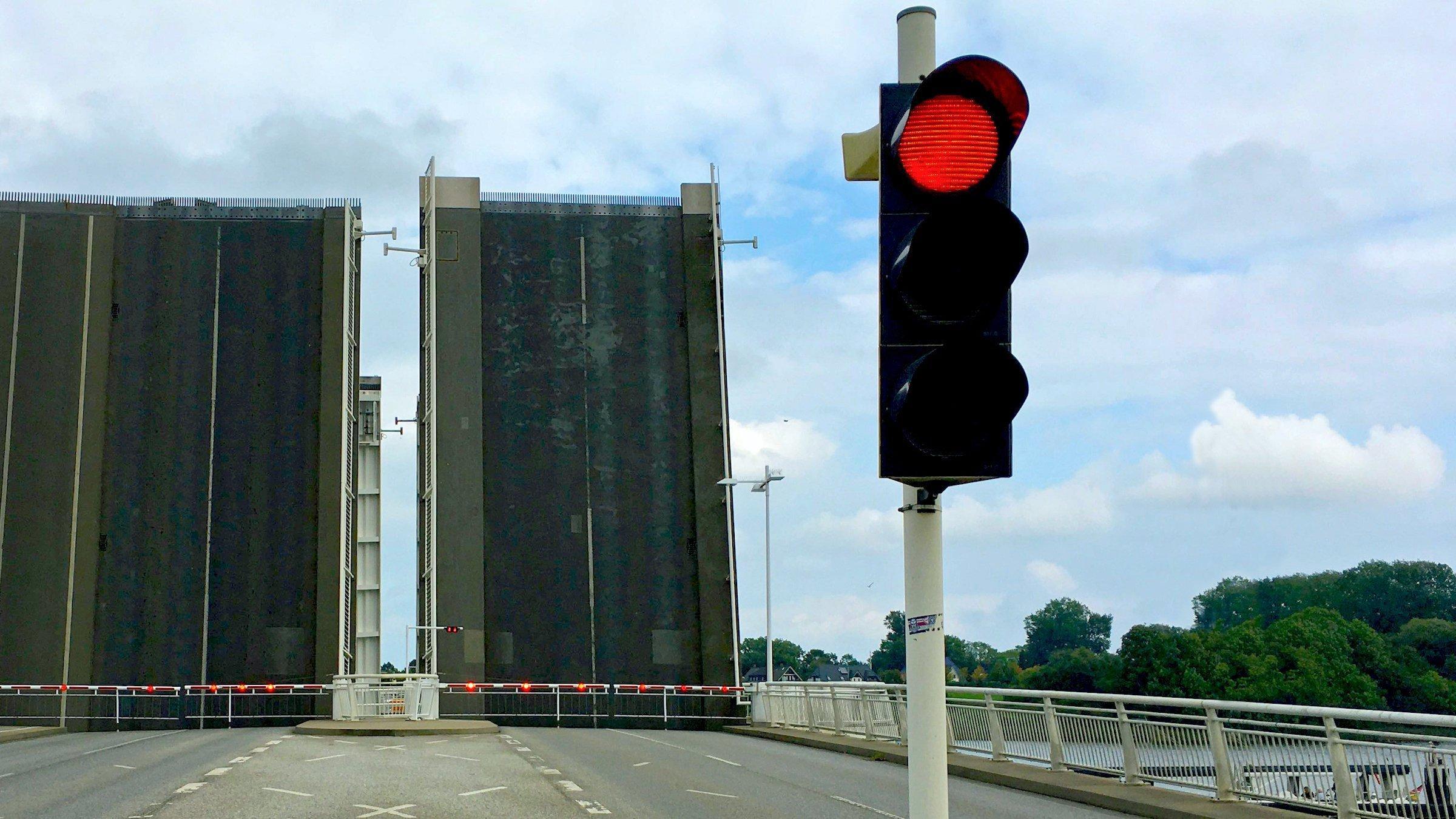 Eine Klappbrücke, hier in Kapseln an der Schlei, ist hochgeklappt, davor sperrt eine rote Ampel die Straße für den Verkehr.