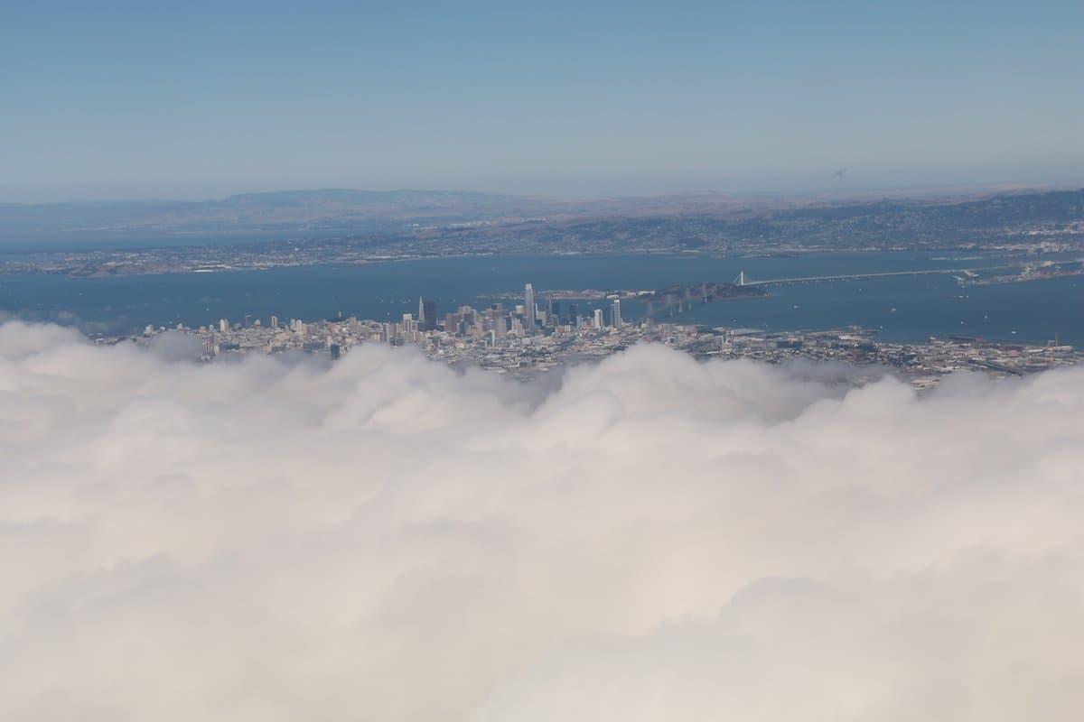 Blick aus dem Flugzeug-Fenster. Durch eine Wolkenlücke erkennt man die Innenstadt von San Francisco Oakland-Bay-Brücke.  Abschied von San Francisco mit Blick auf die Skyline und die Oakland-Bay-Bridge. Bleiben die Versprechen, die in der Stadt abgegeben wurden, nur wolkige Worte?