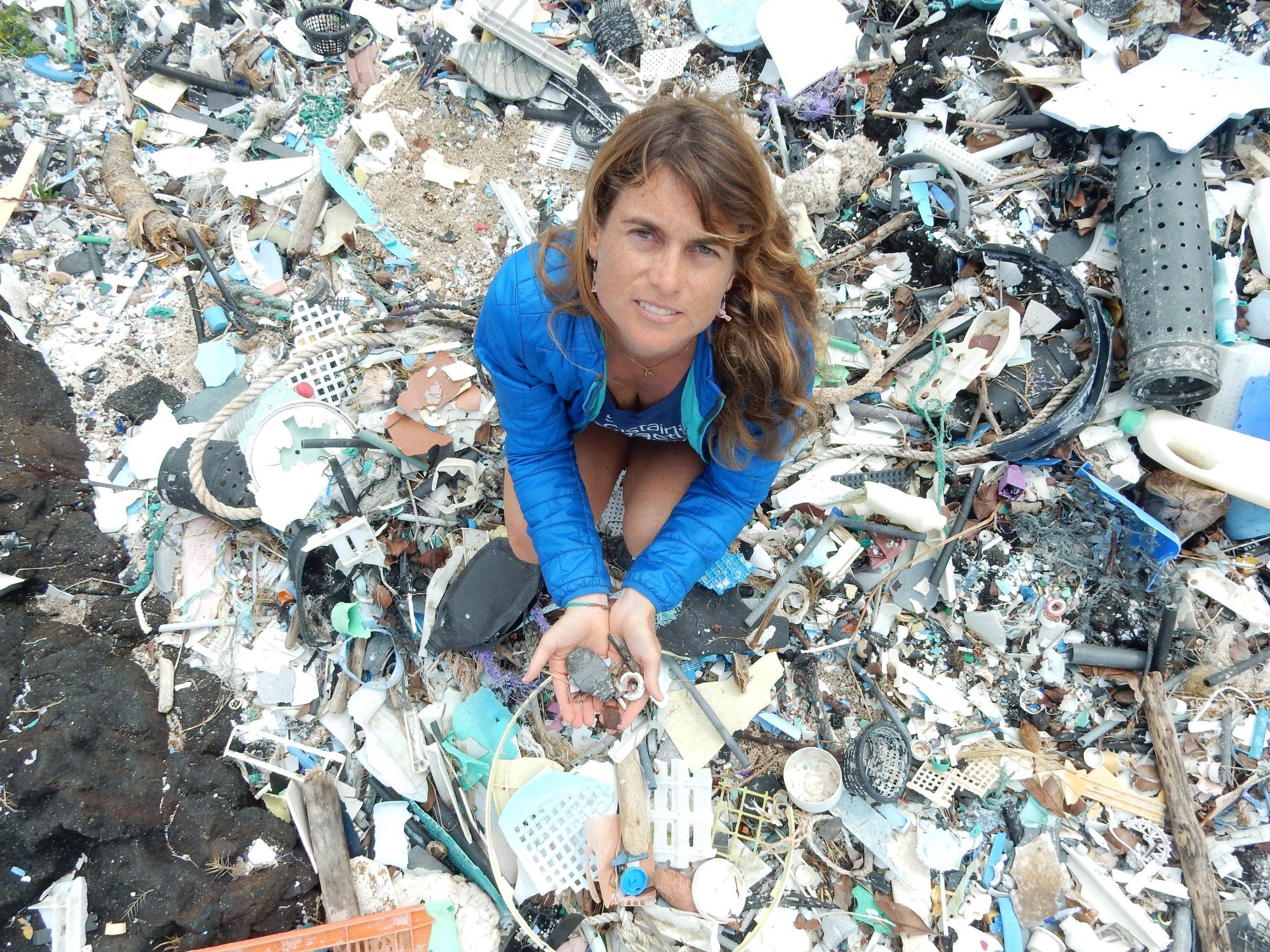 Die Forscherin steht auf einem mit Plastik verschmutzten Strand und hält es auch in ihren Händen.