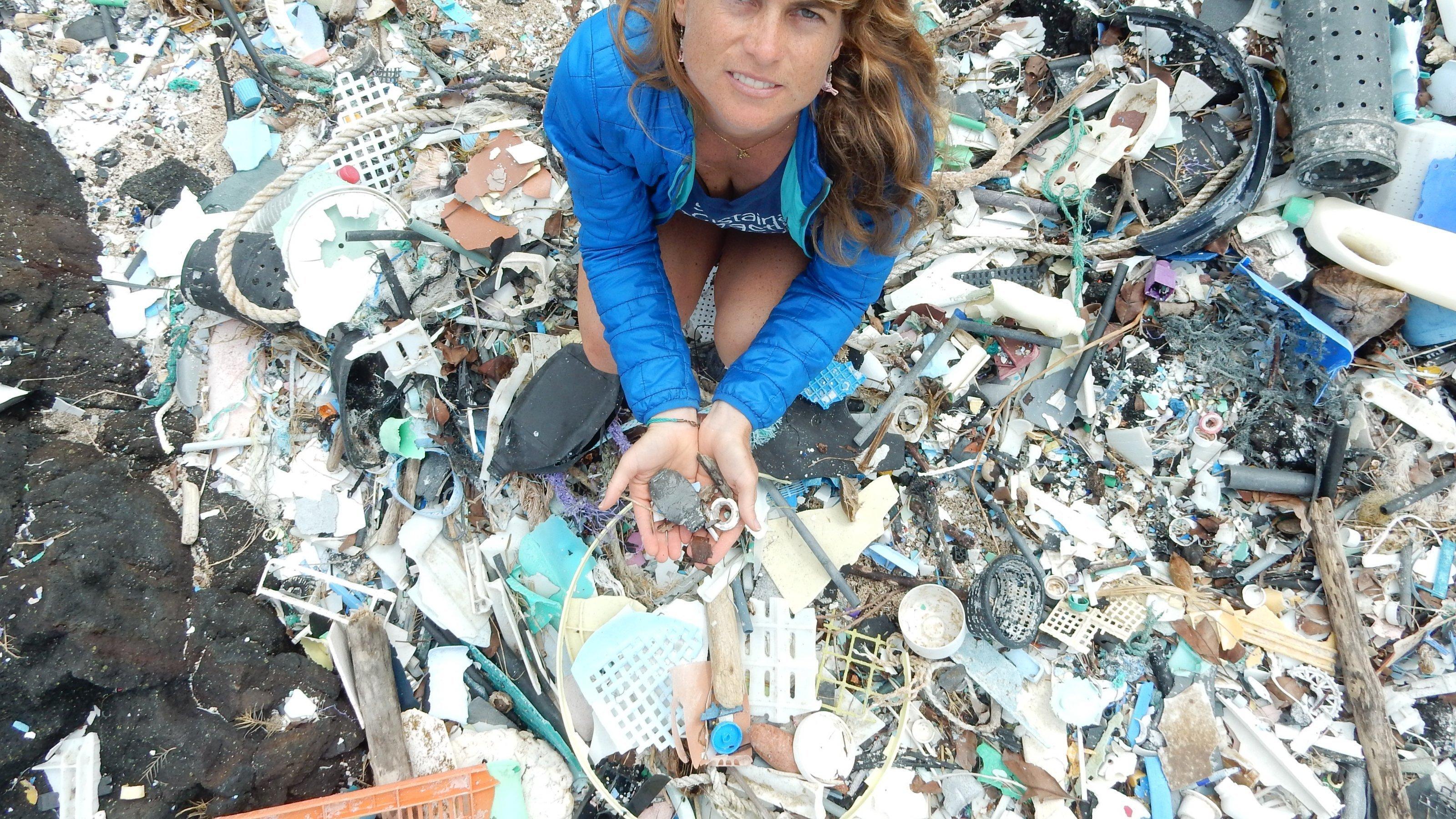 Die Forscherin steht auf einem Berg von angespülten Plastikresten.