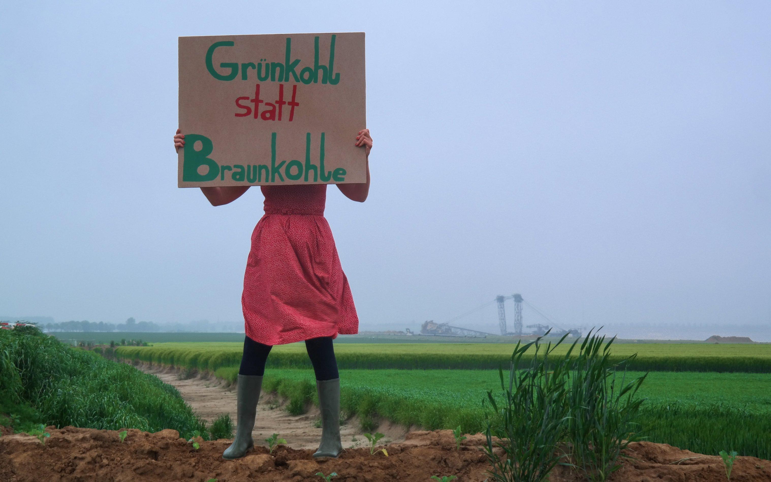 """Eine Person in rotem Rock und Gummistiefeln steht vor einem grünen Feld und hält ein Pappschild mit der Aufschrift """"Grünkohl statt Braunkohle"""" hoch."""