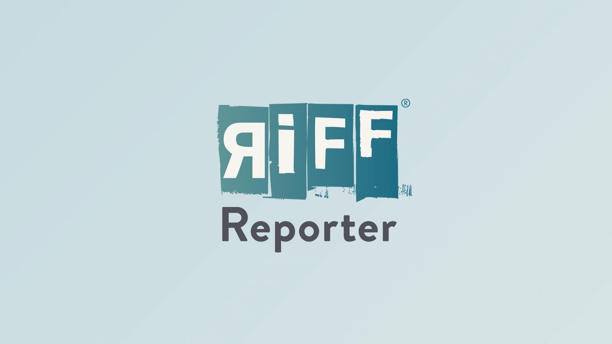 Ein Schneeleopard schaut in einem Gebirge abwärts.