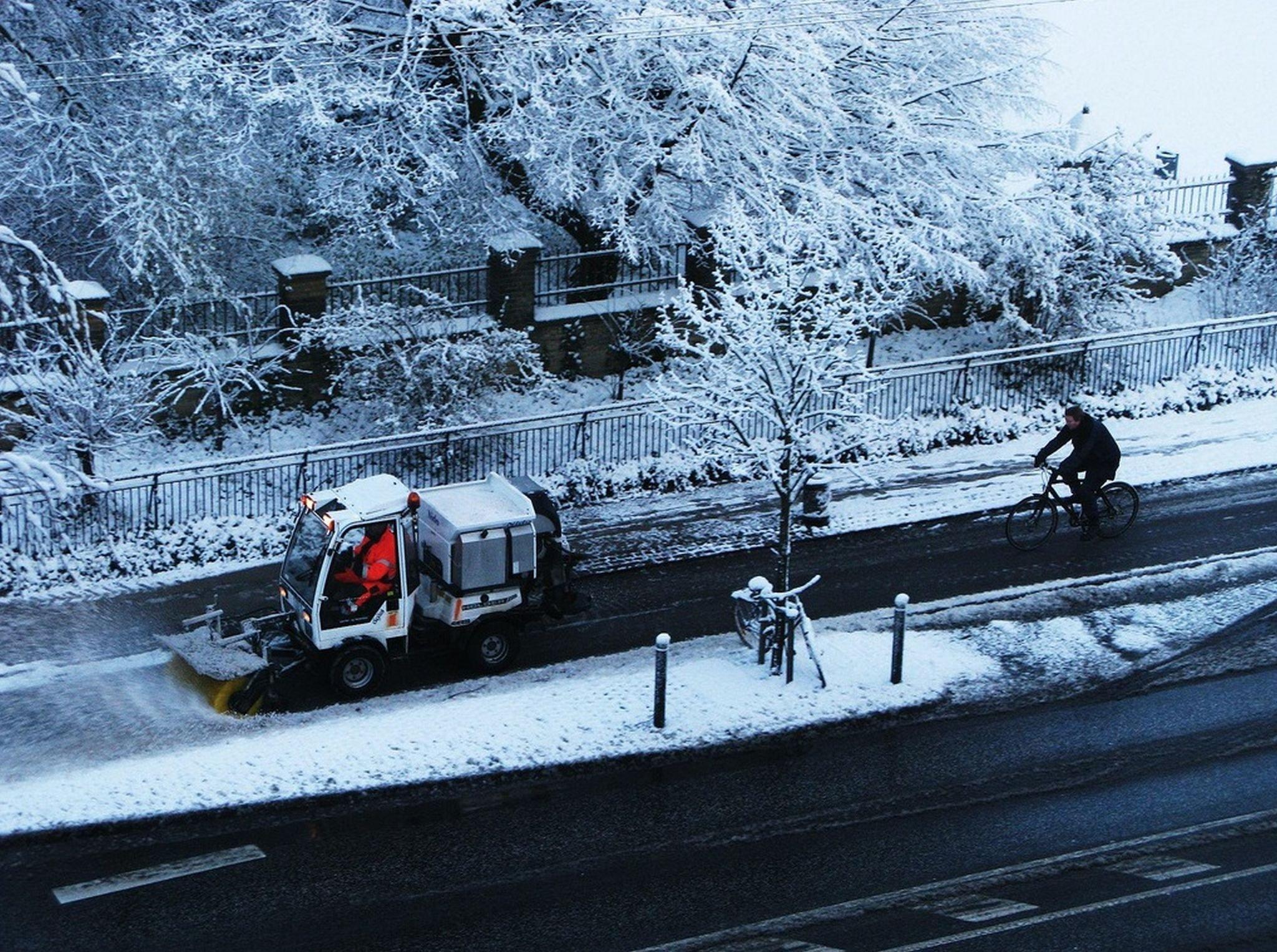Ein Schneepflug räumt einen verschneiten Radweg.