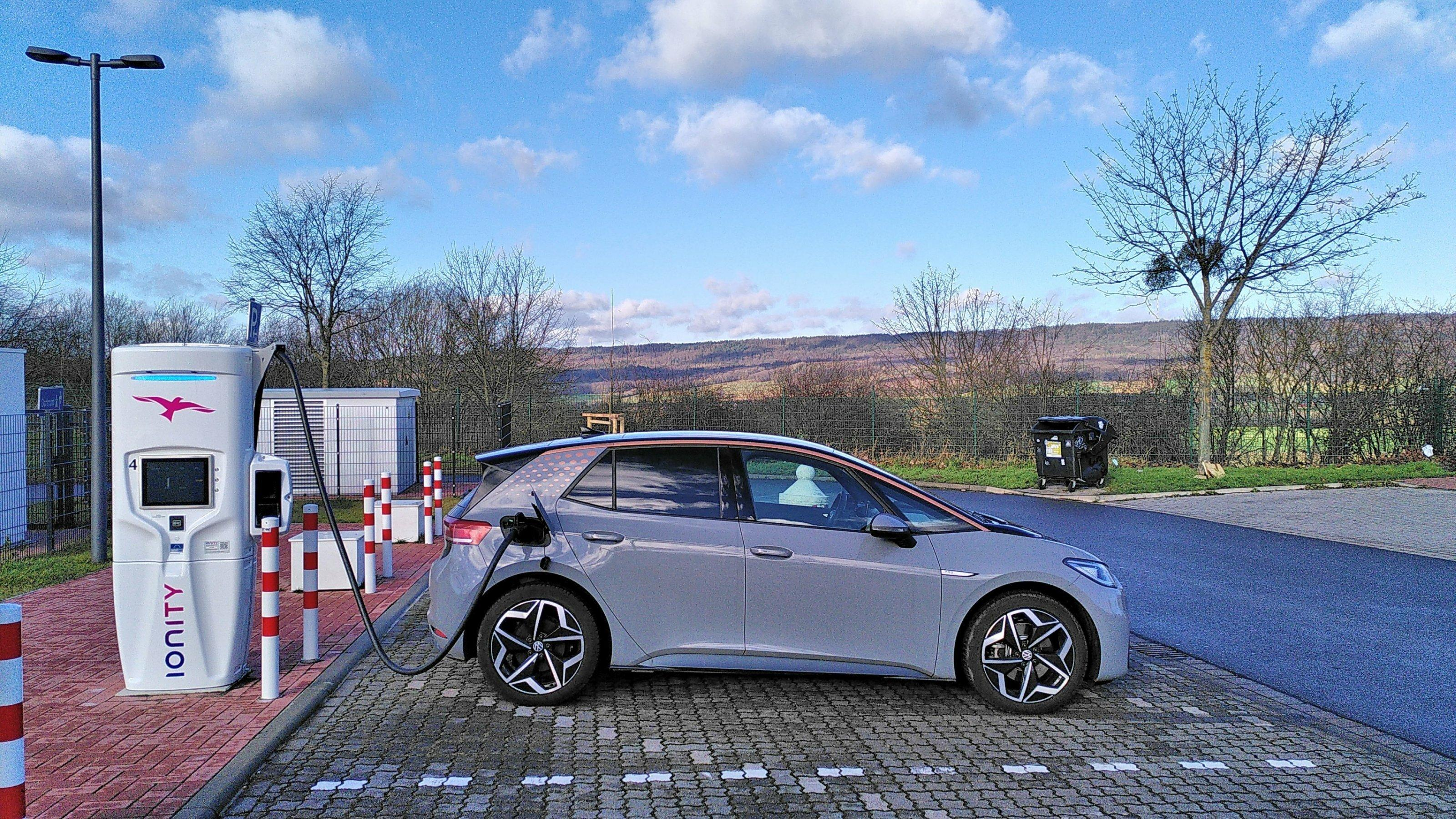Ein Elektroauto ist auf einem Rastplatz an eine Ladestation angeschlossen.