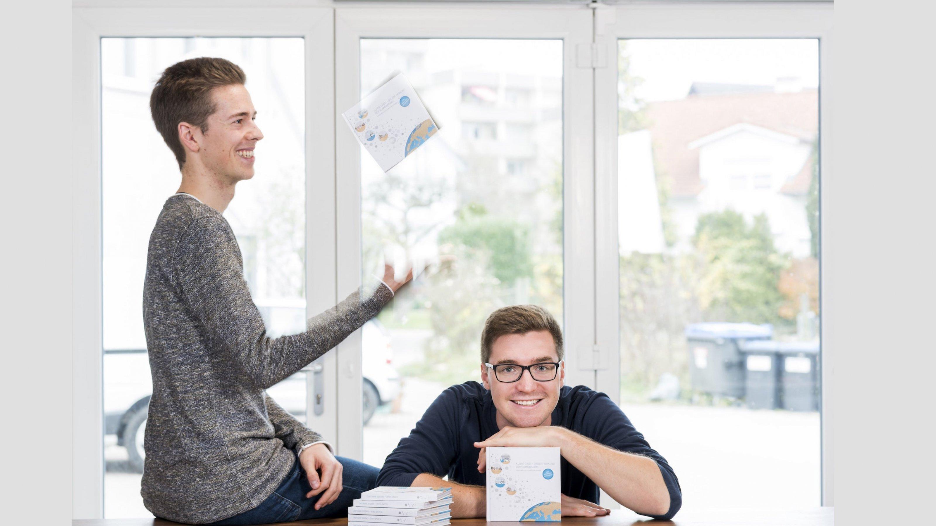 Christian Serrer (links) sitzt auf der Tischkarte und wirft das gemeinsame Buch wie einen Tennisball in die Luft, David Nelles stützt Hände und Kopf auf das Werk